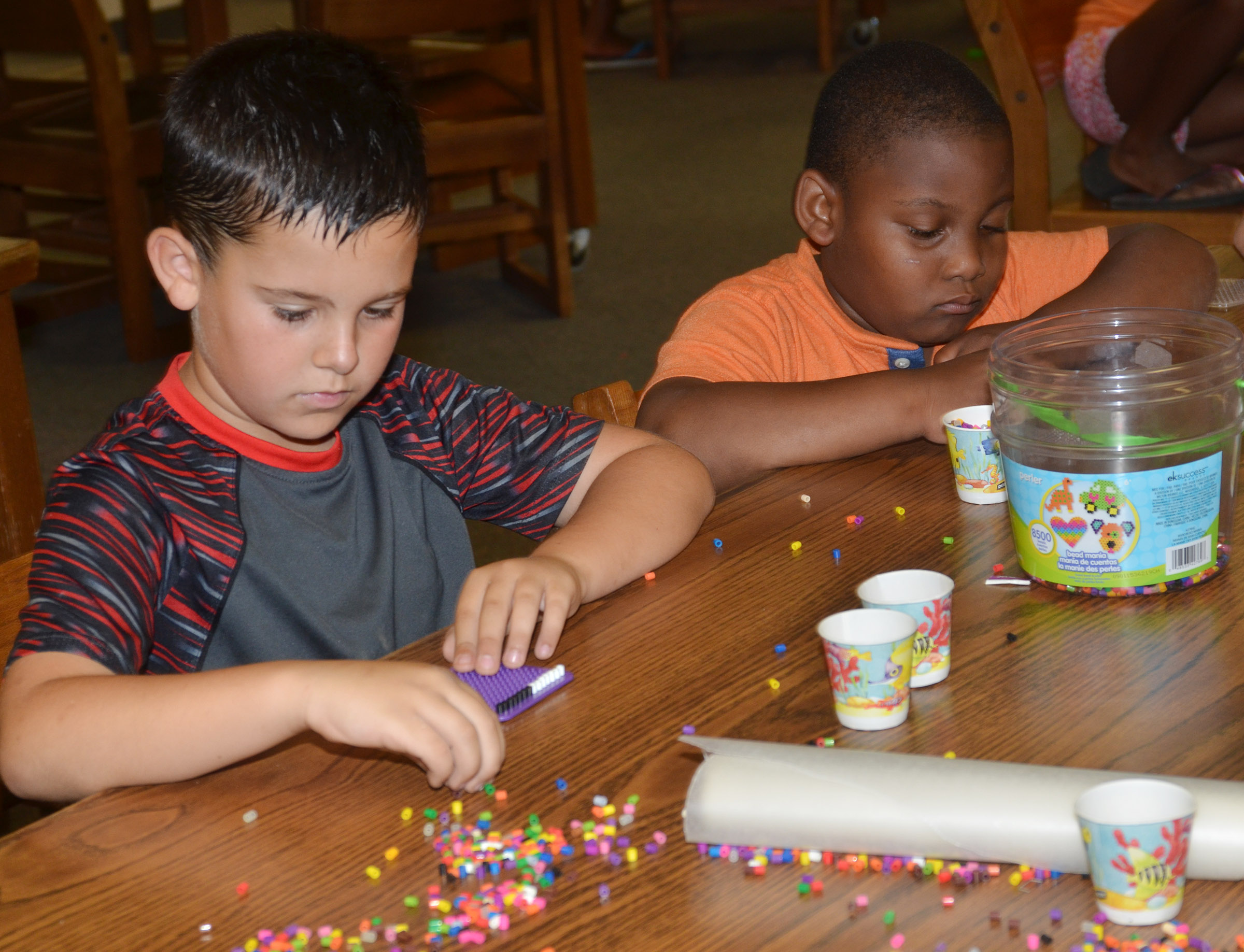 CES second-grader Damien Clark, at left, and kindergartener Malachi Conner make bead art.