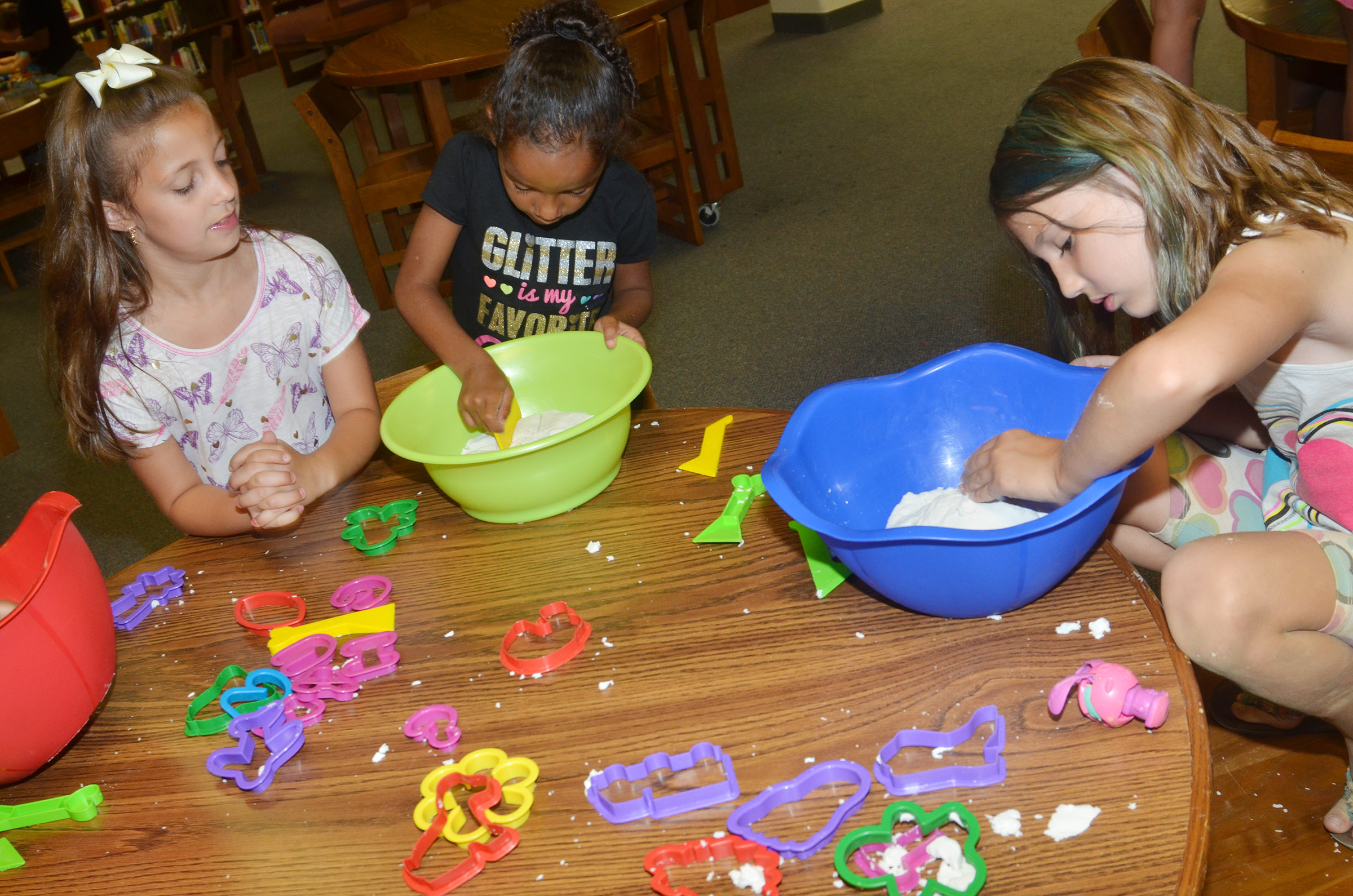 From left, CES first-grader Lillian Martin, kindergartener Kaylee Thompson and second-grader Kairi Tucker play with sand.