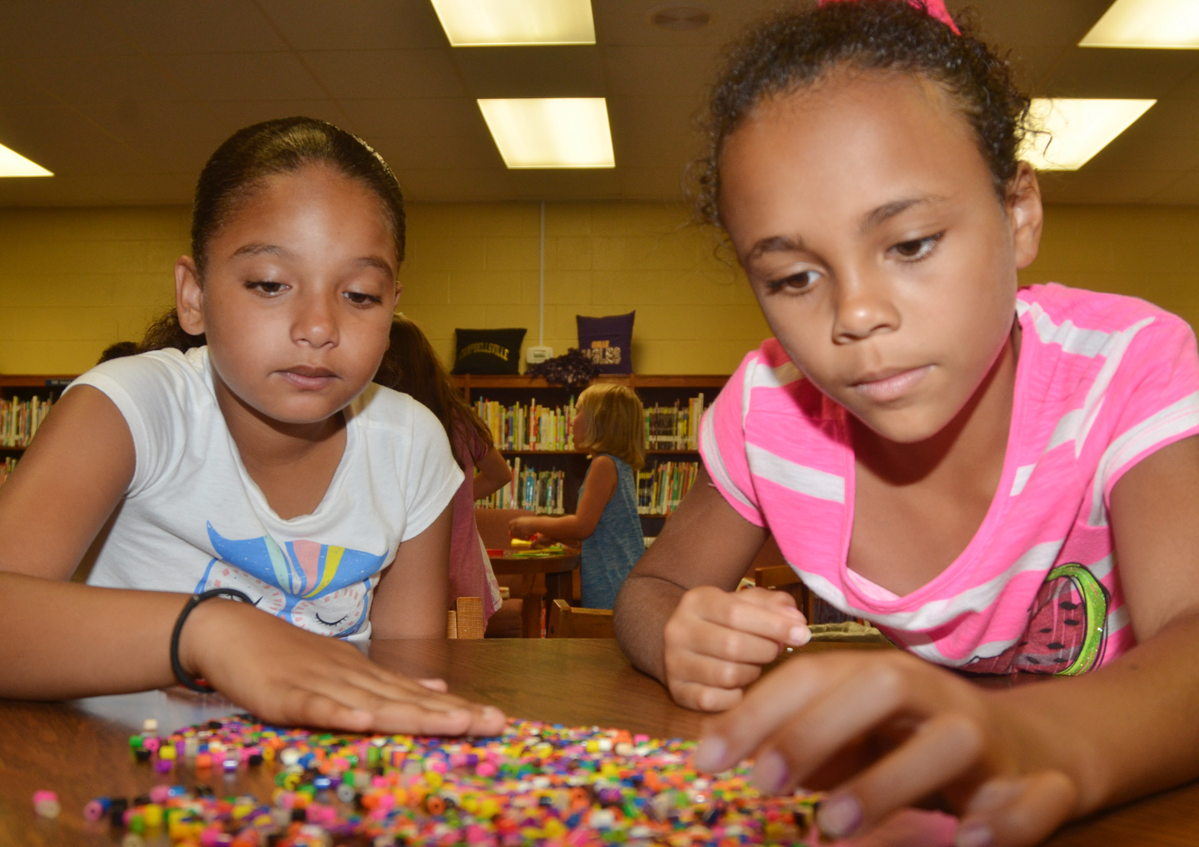 CES third-grader Aleecia Knezevic, at left, and second-grader Braelyn Taylor make bead art.
