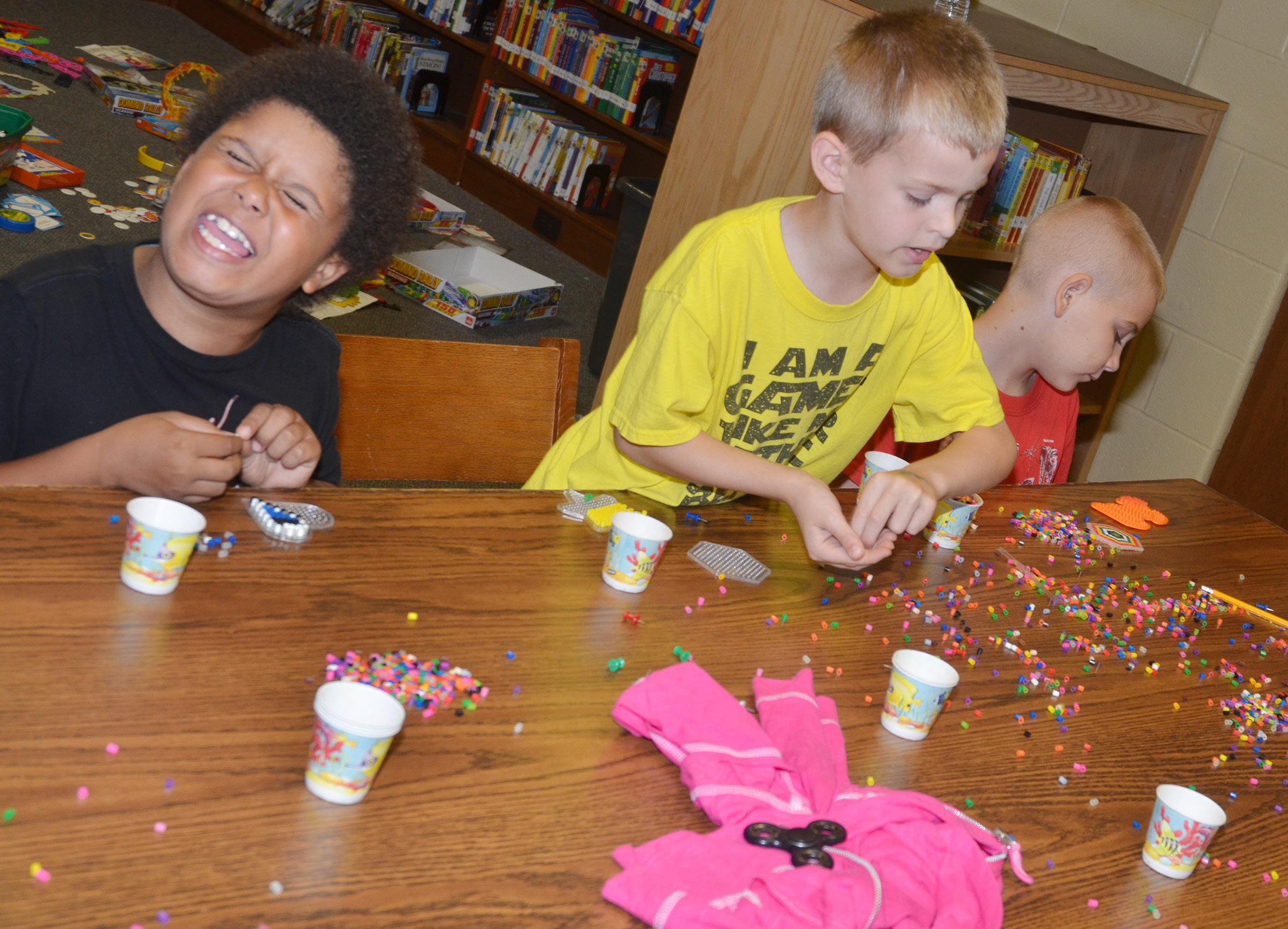 CES first-grader Navon Copeland is all smiles as he and first-grader Logan Weddle, center, and second-grader Joseph Greer make bead art.