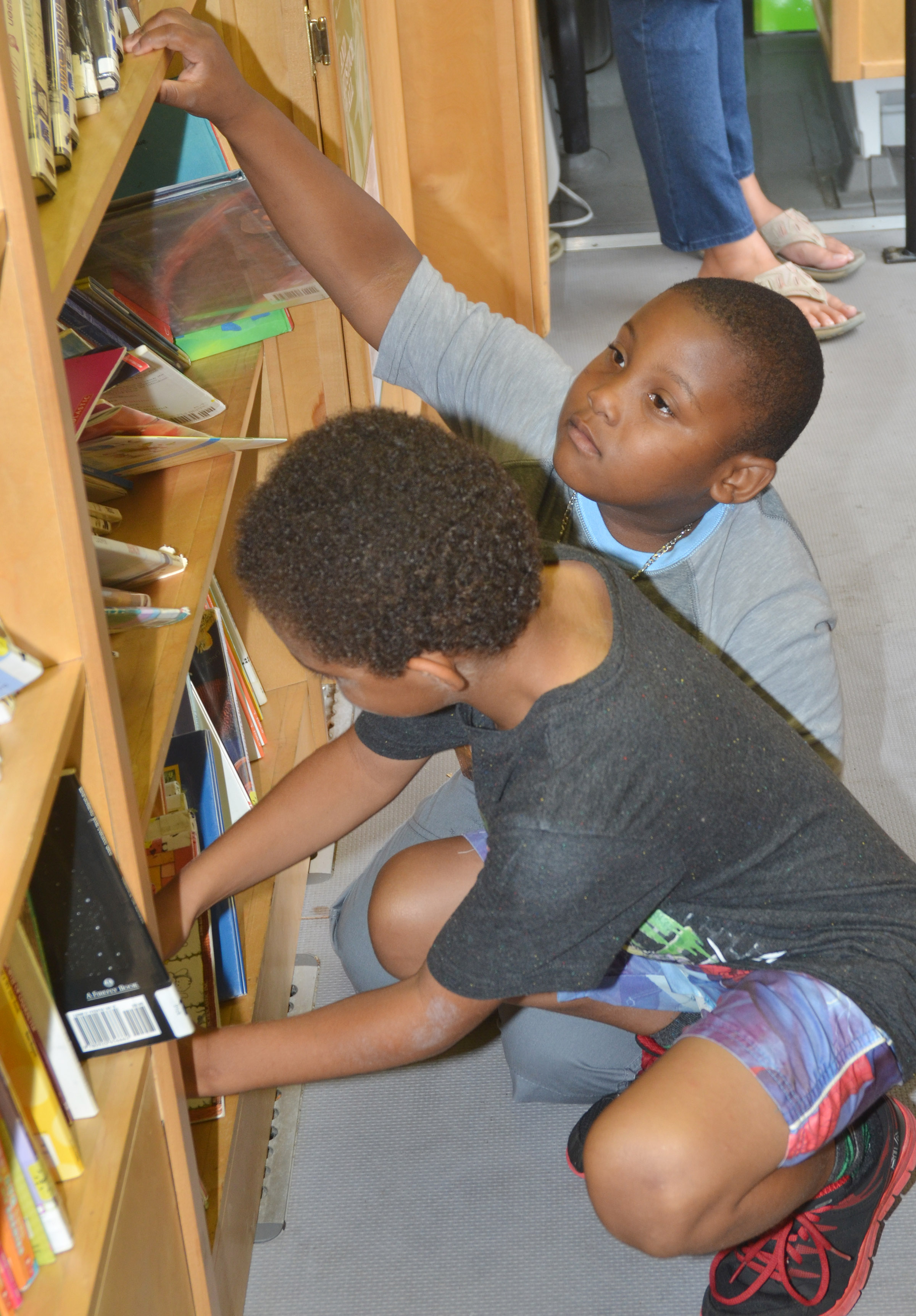 CES kindergartners Quincy Travis, at left, and Malachi Conner search for books on the bookmobile.