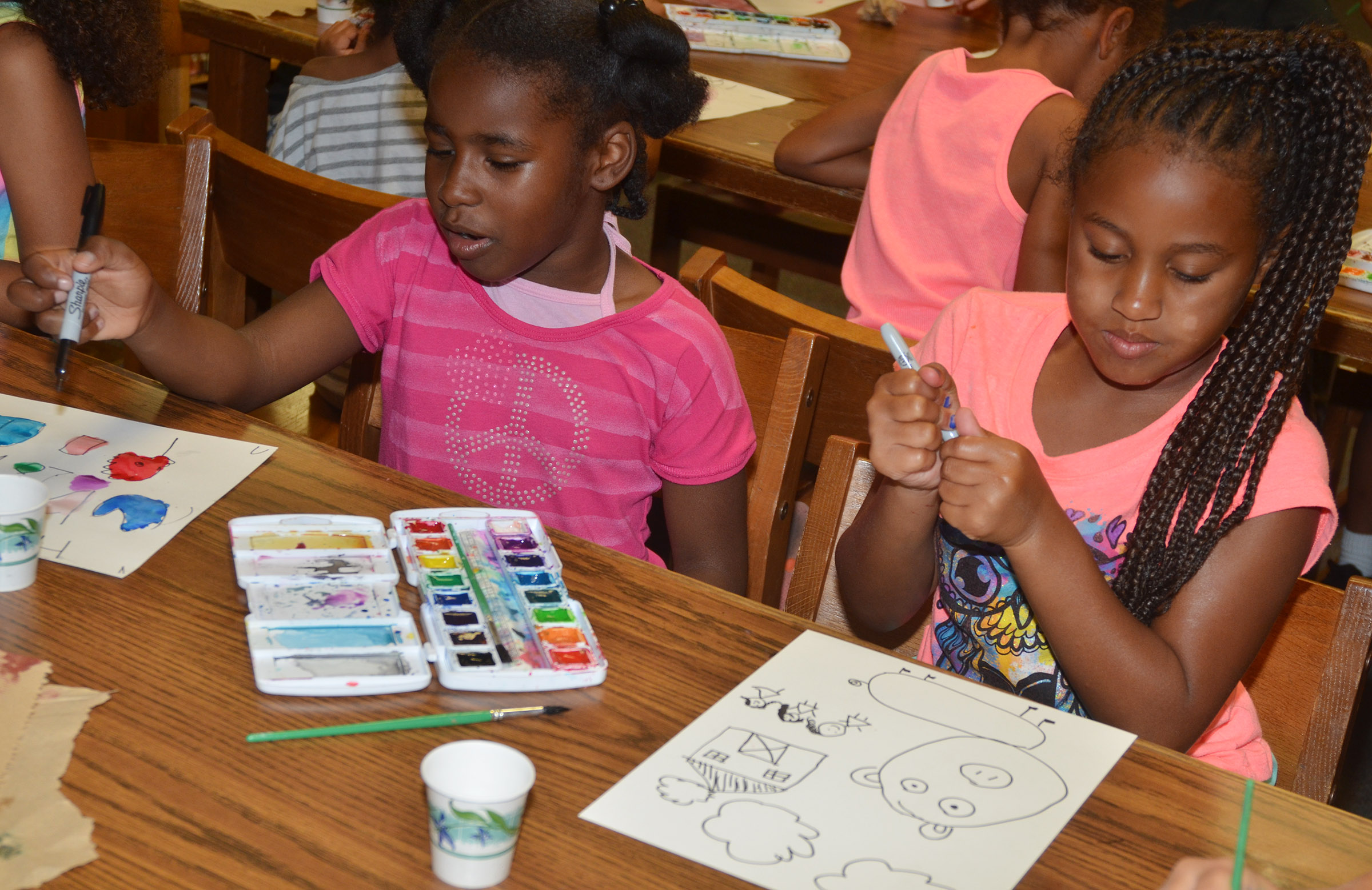 CES first-graders Destini Gholston, at left, and Kadance Ford paint.