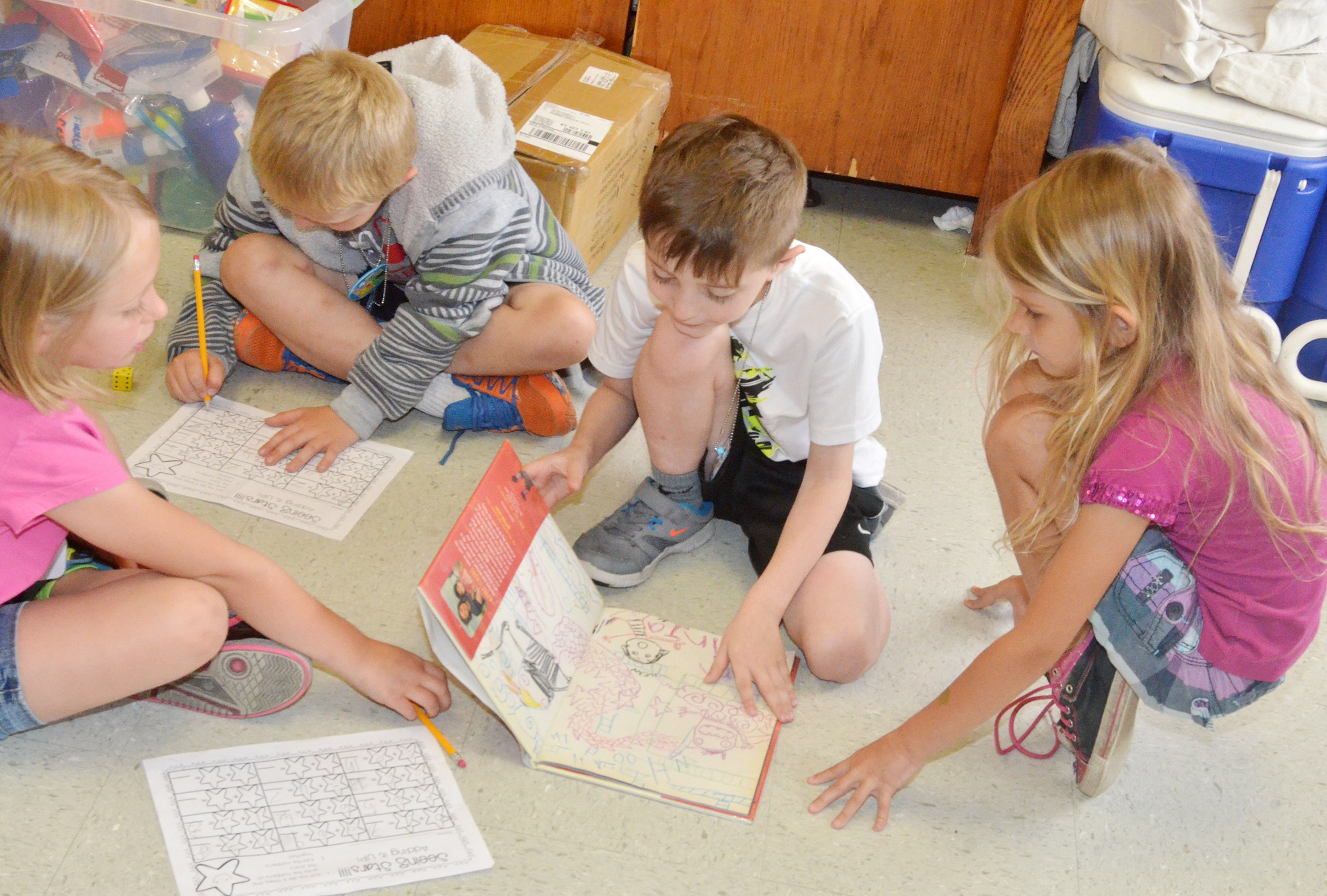 CES kindergarteners, from left, LeeAnna Garvin, Trenton Harris, Caleb Goodson and Gracie Gebler read and practice their math skills together.