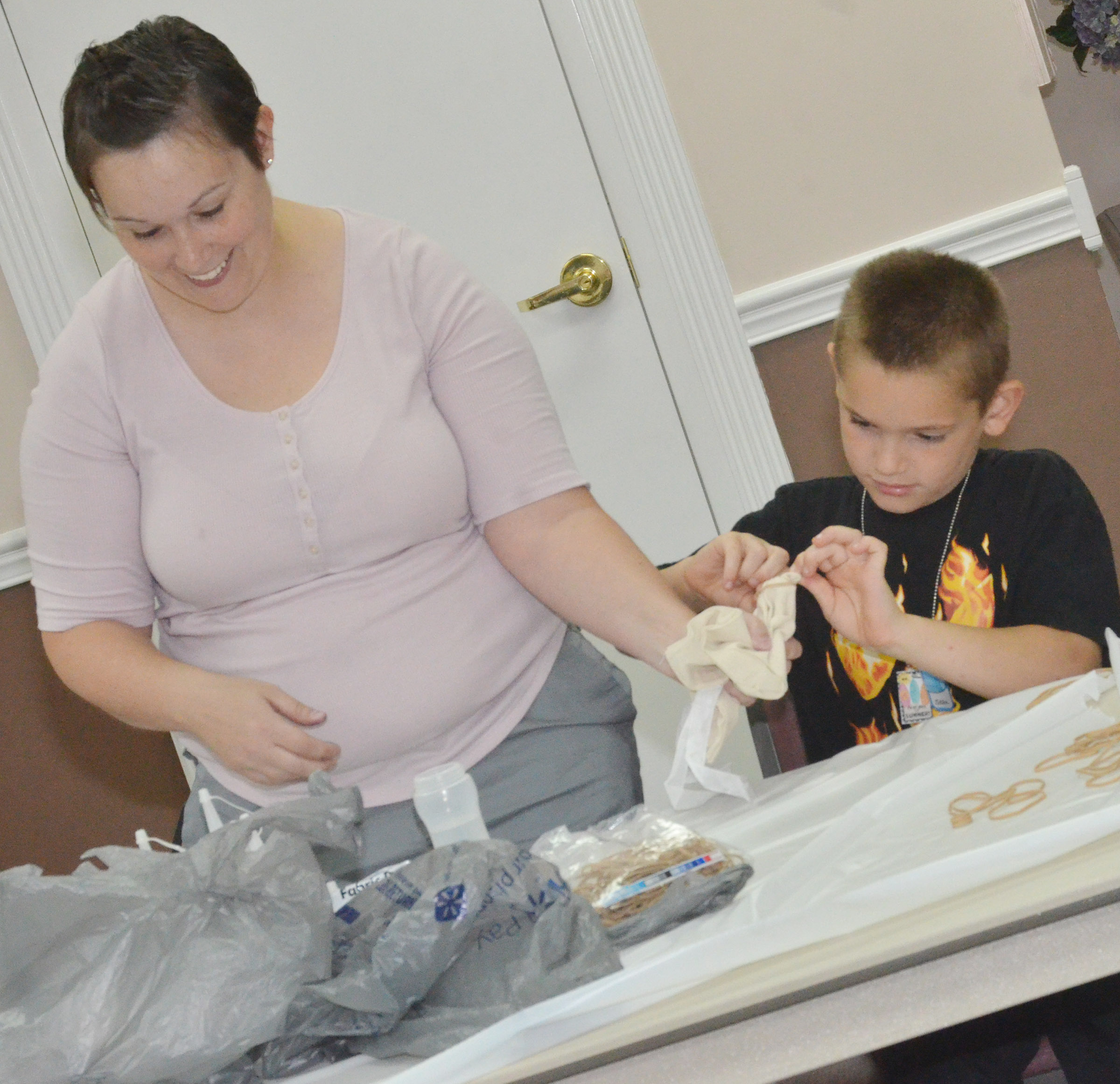 CES Wings Express Director Amanda Barnett helps second-grader Sean Welch tie knots in his bag so he can tie-dye it.
