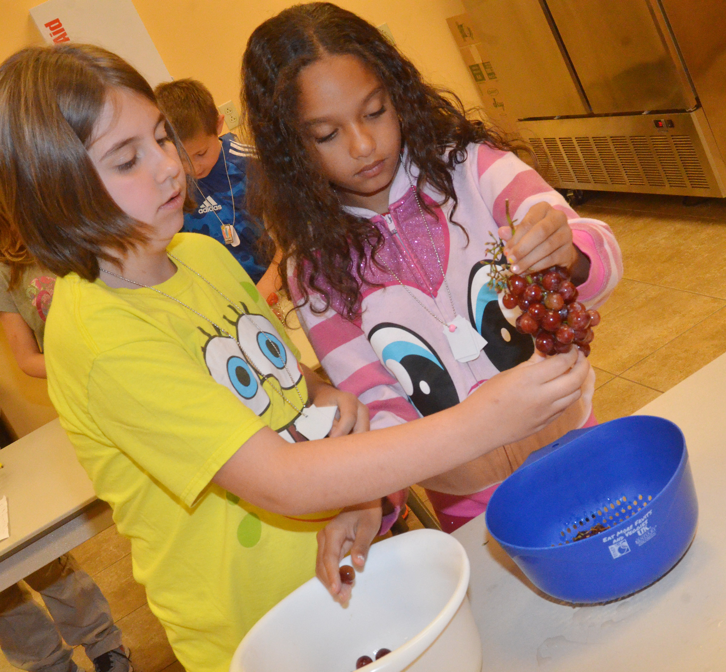 CES third-graders Adrianna Garvin, at left, and Alyssa Knezevic prepare grapes as they make a healthy snack.