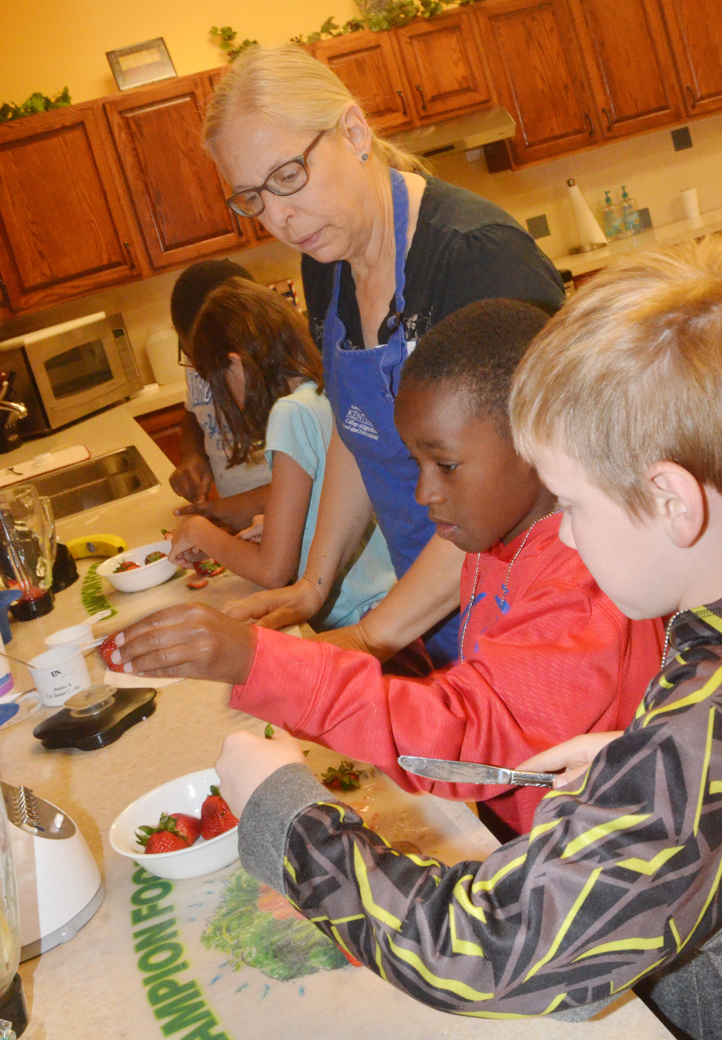 Angie Freeman, expanded foods and nutrition program assistant at Taylor County Extension Office, helps CES Wings Express students John Gholston, center, and Connor Coots, third-graders, prepare fruit as they make a healthy snack.