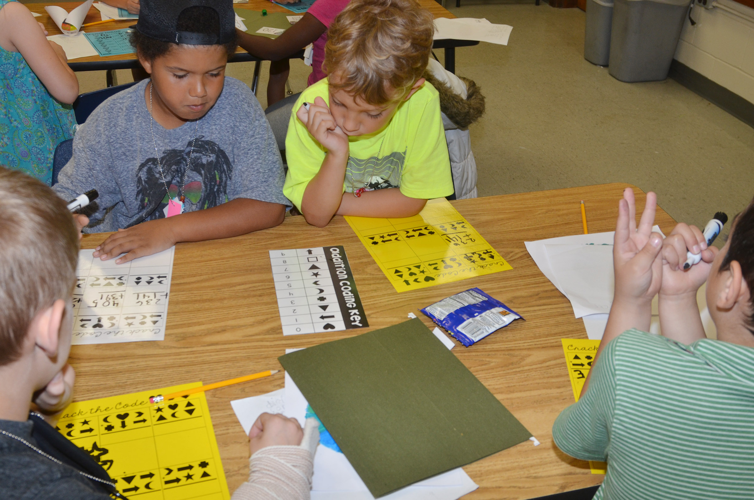 CES first-graders Navon Copeland, at left, and Gabe Prior try to decode some math problems with their classmates.
