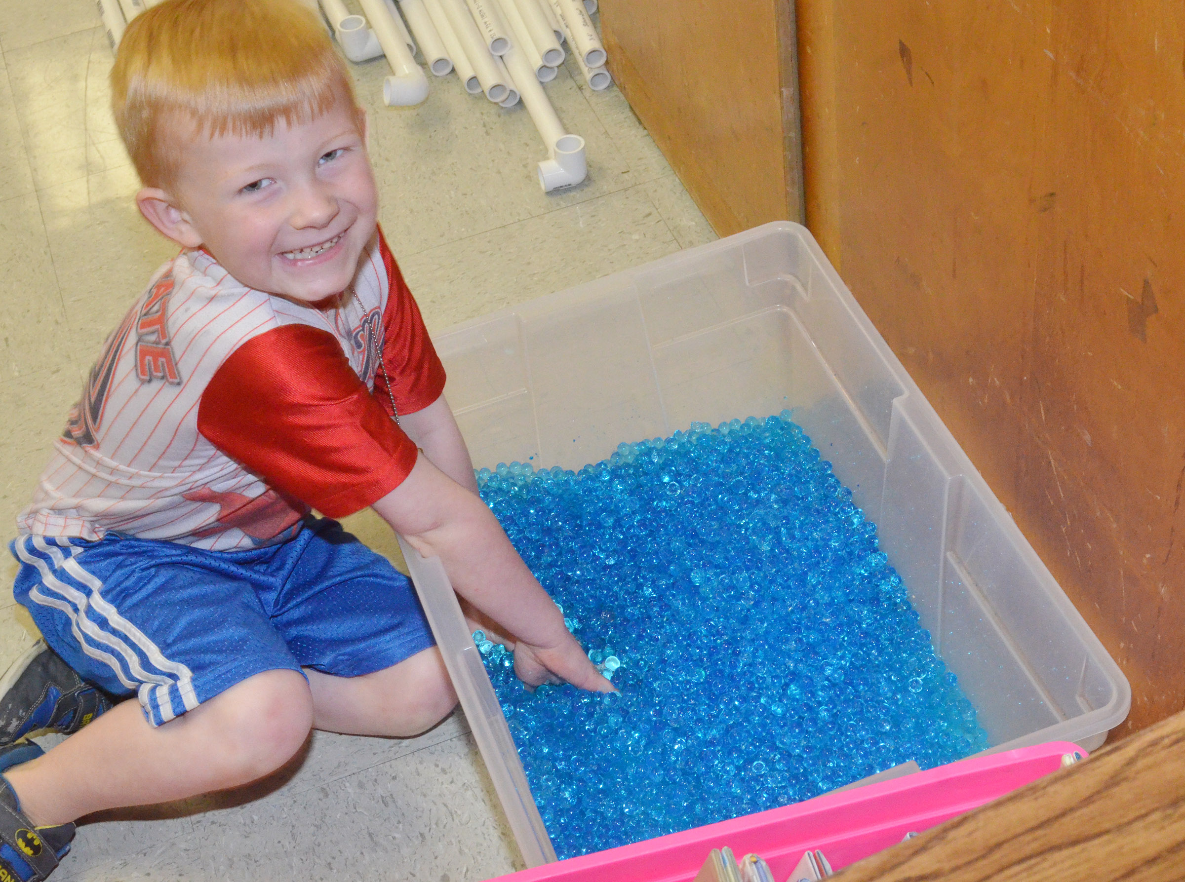 CES kindergartener Jayden Maupin puts his hands in a tub full of beads.