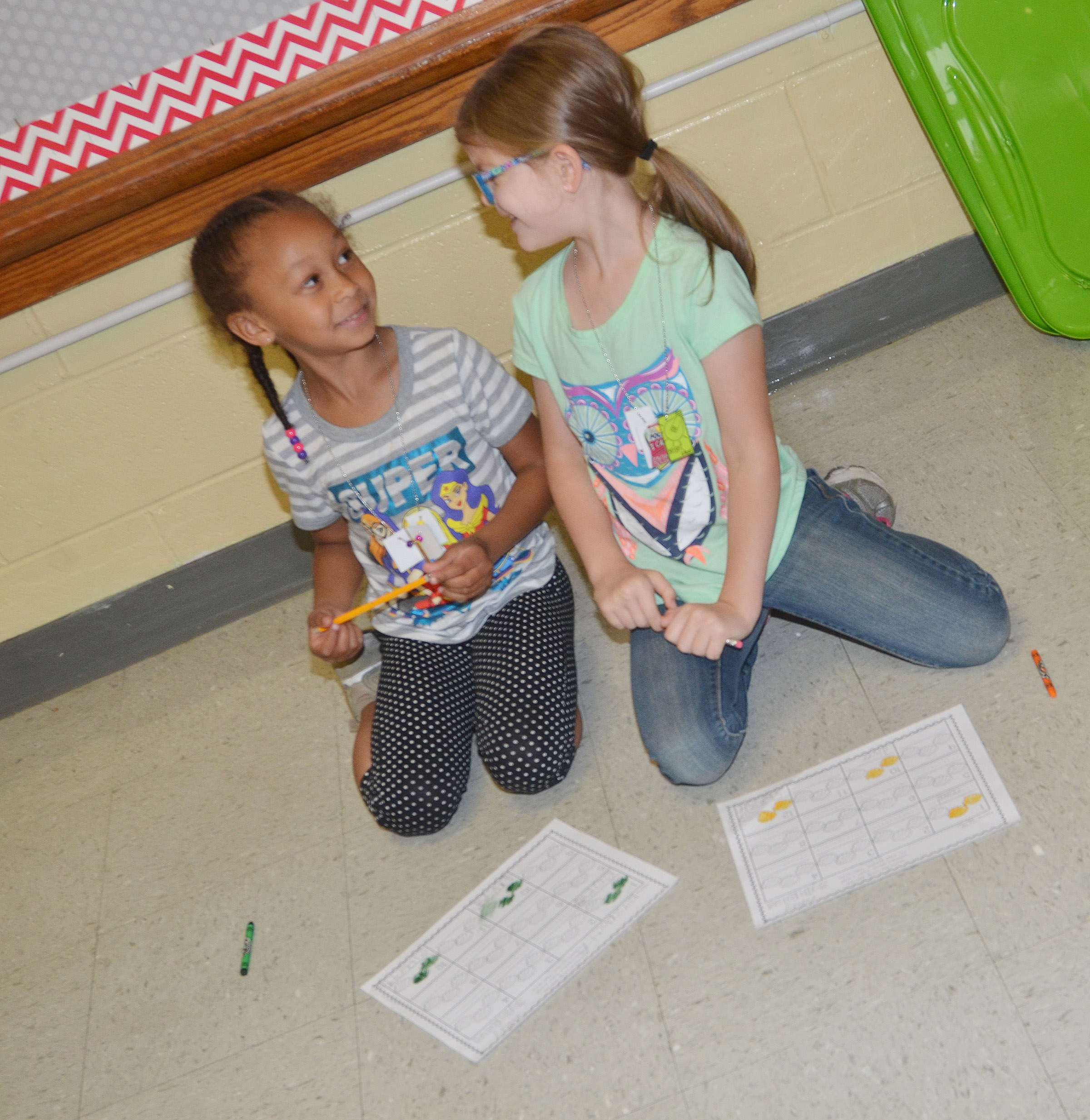 CES kindergarteners Elyzabeth Fisher, at left, and Zoe Weddle share a laugh as they practice counting.