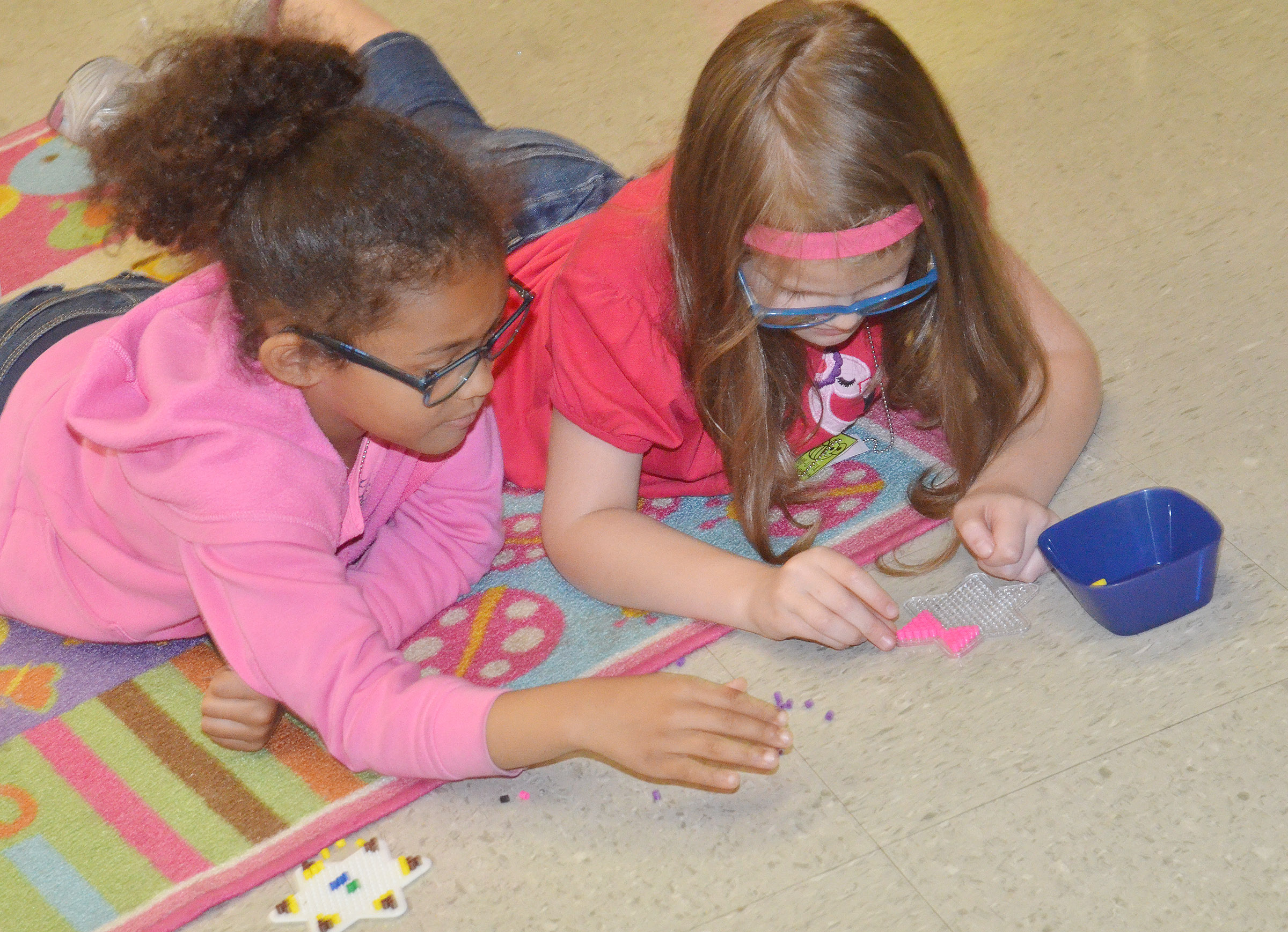 CES kindergarteners Marlee Dickens, at left, and Zoe Weddle make bead art together.