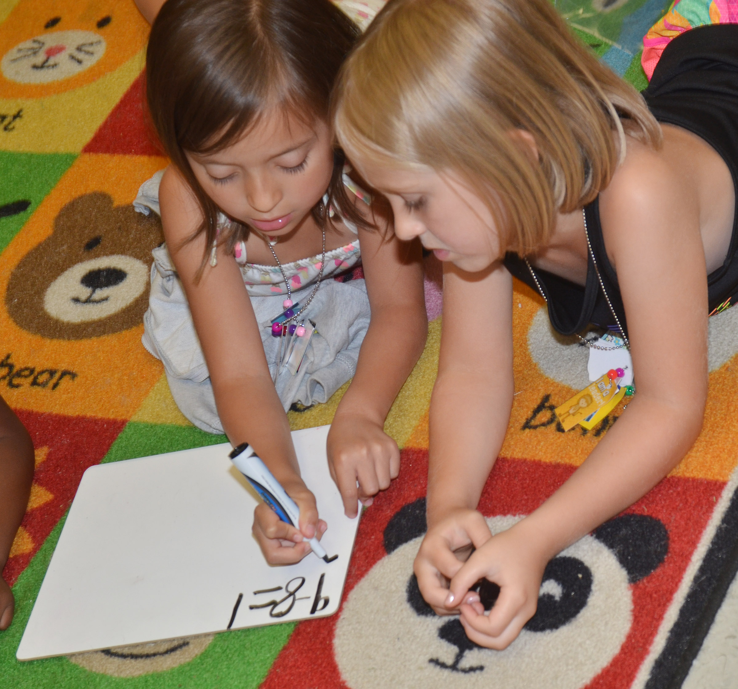 CES kindergarteners Gabriella Tate, at left, and LeeAnna Garvin work a math problem together.