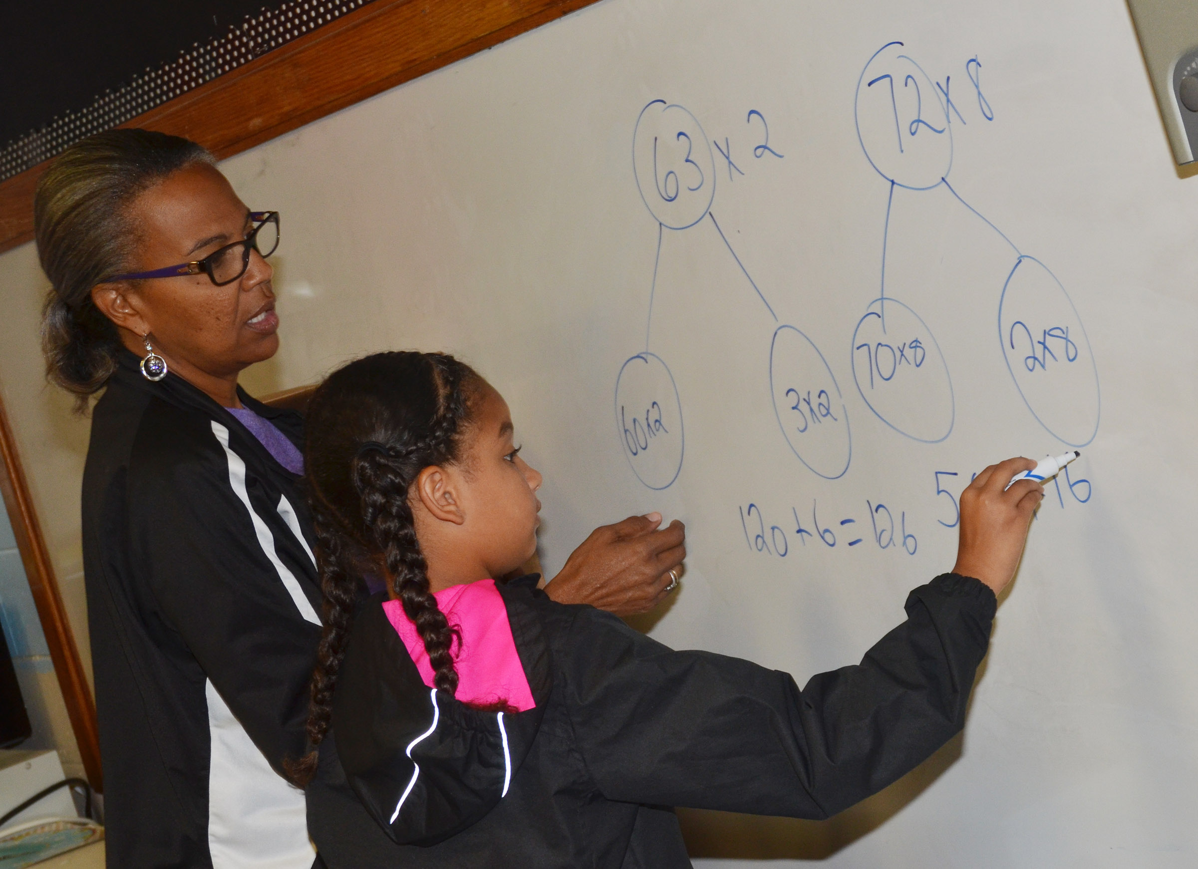 CES Wings Express assistant Doretha Sanders helps Narissa Barnett work a math problem.