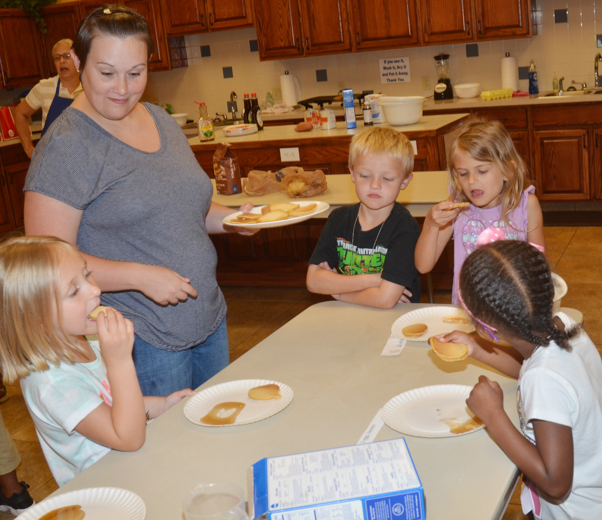 CES Wings Express Director Amanda Barnett serves pancakes to kindergarten students.