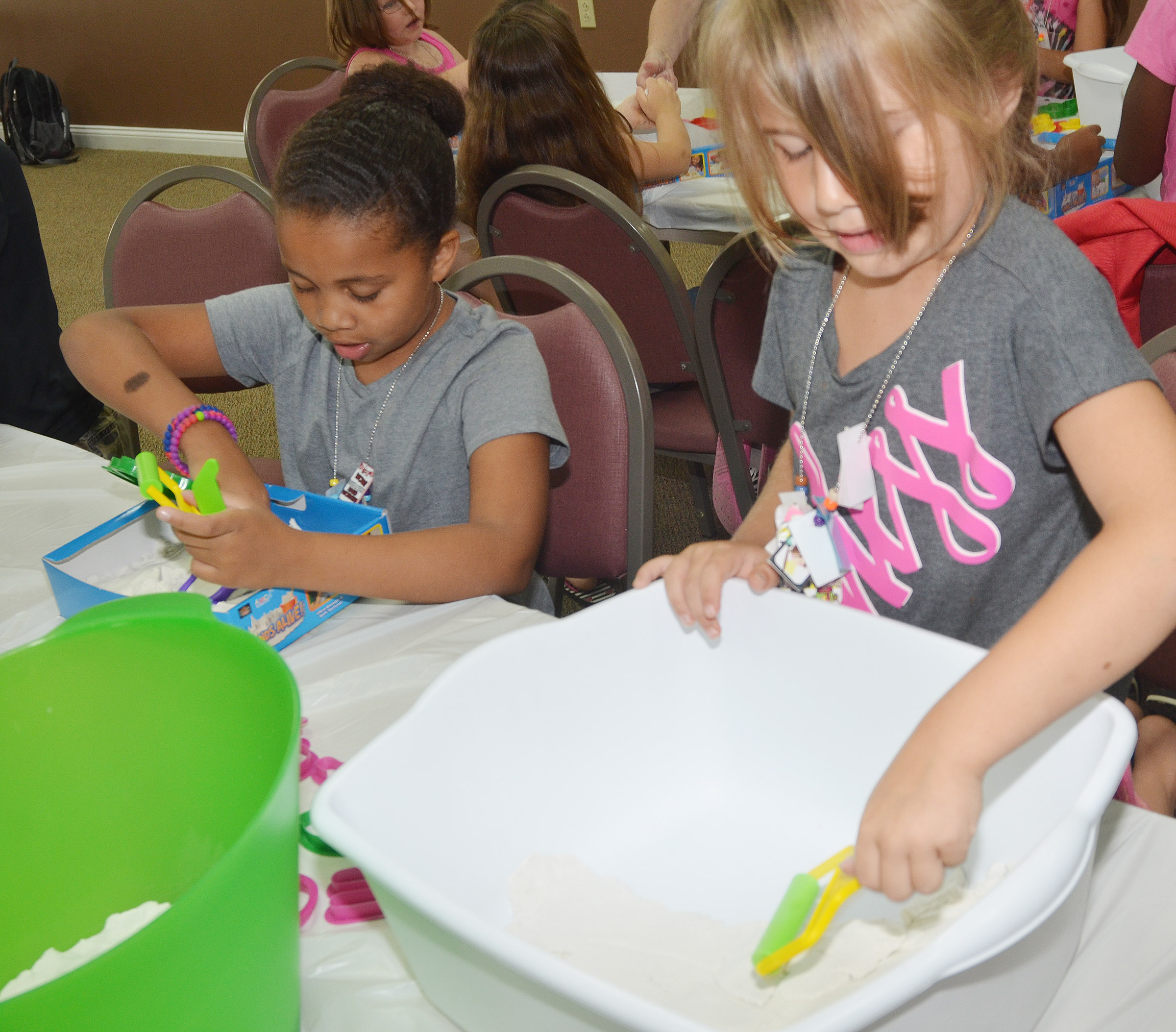 CES first-graders Journey Webb, at left, and Kenady Hayes play with sand.