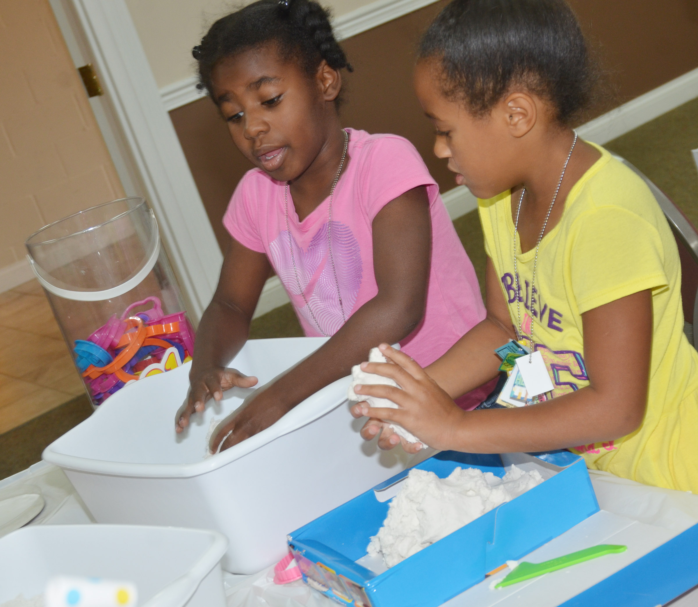 CES first-graders Destini Gholston, at left, and Kadance Ford talk as they make shapes in sand.