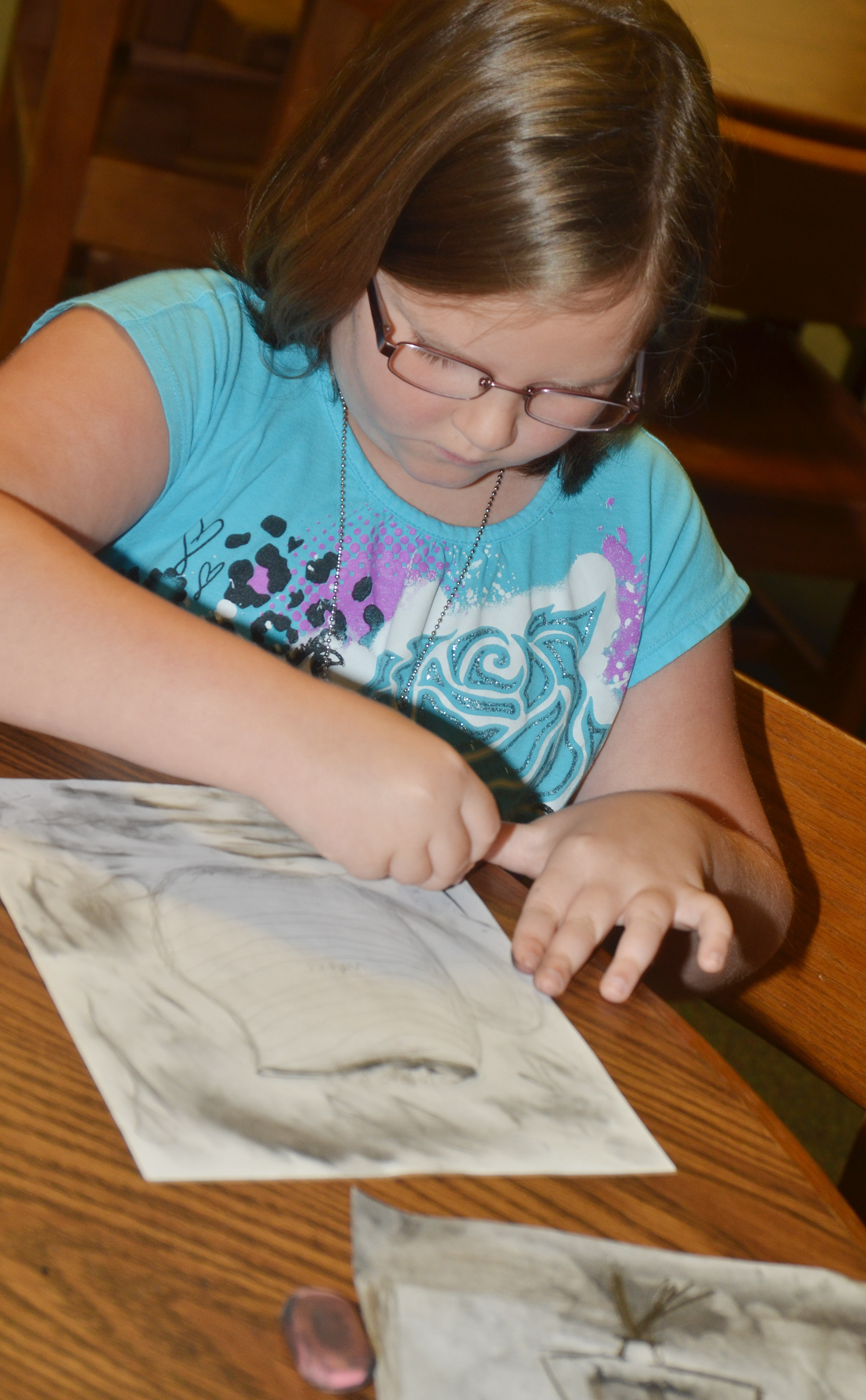 CES first-grader Justice Albrecht draws with charcoal.