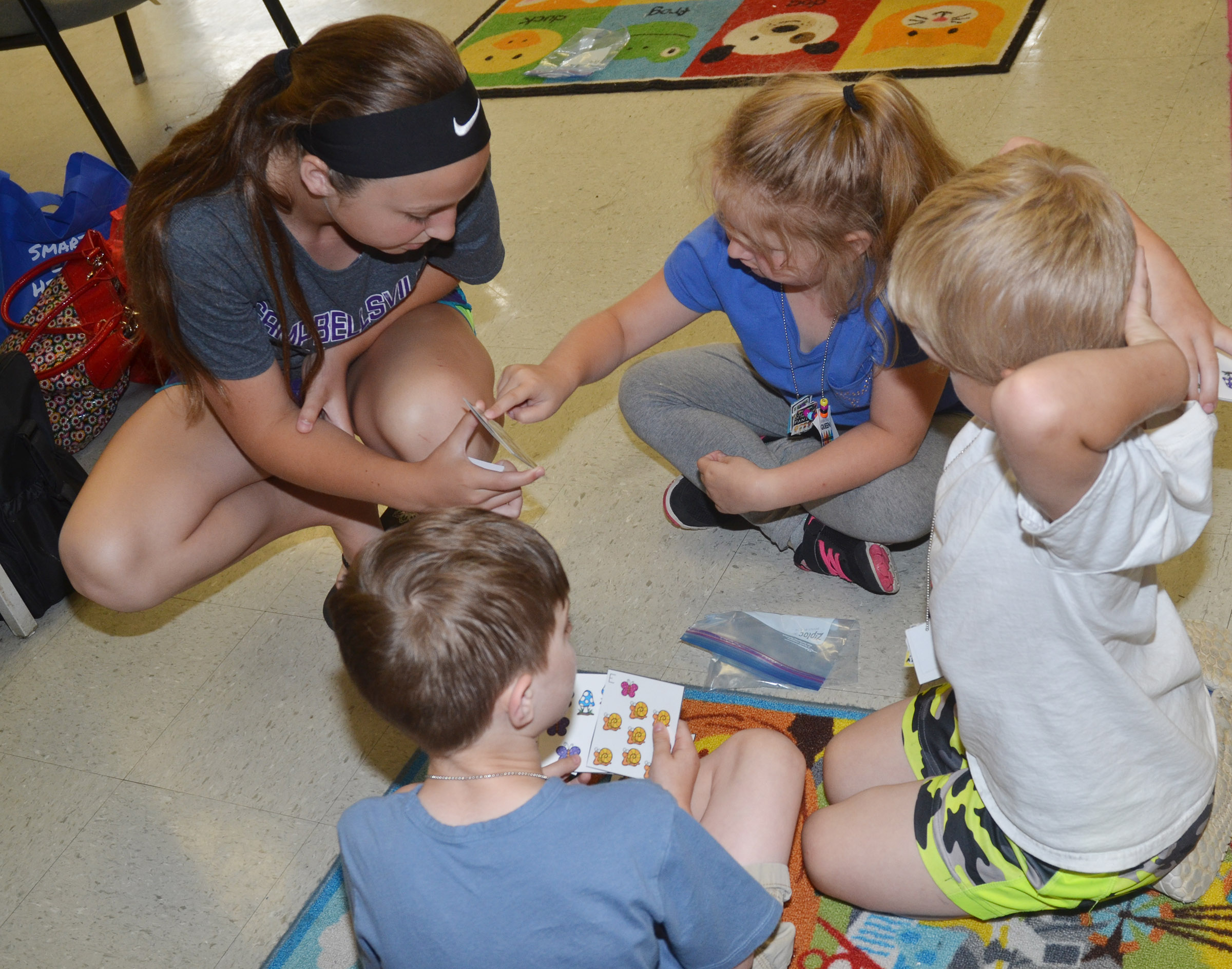 Campbellsville Middle School seventh-grader Lainey Watson, who volunteered to help with the CES Wings Express summer program, helps, from left, kindergarteners Caleb Goodson, Laurna McKenzie and Tristian Harris practice counting.