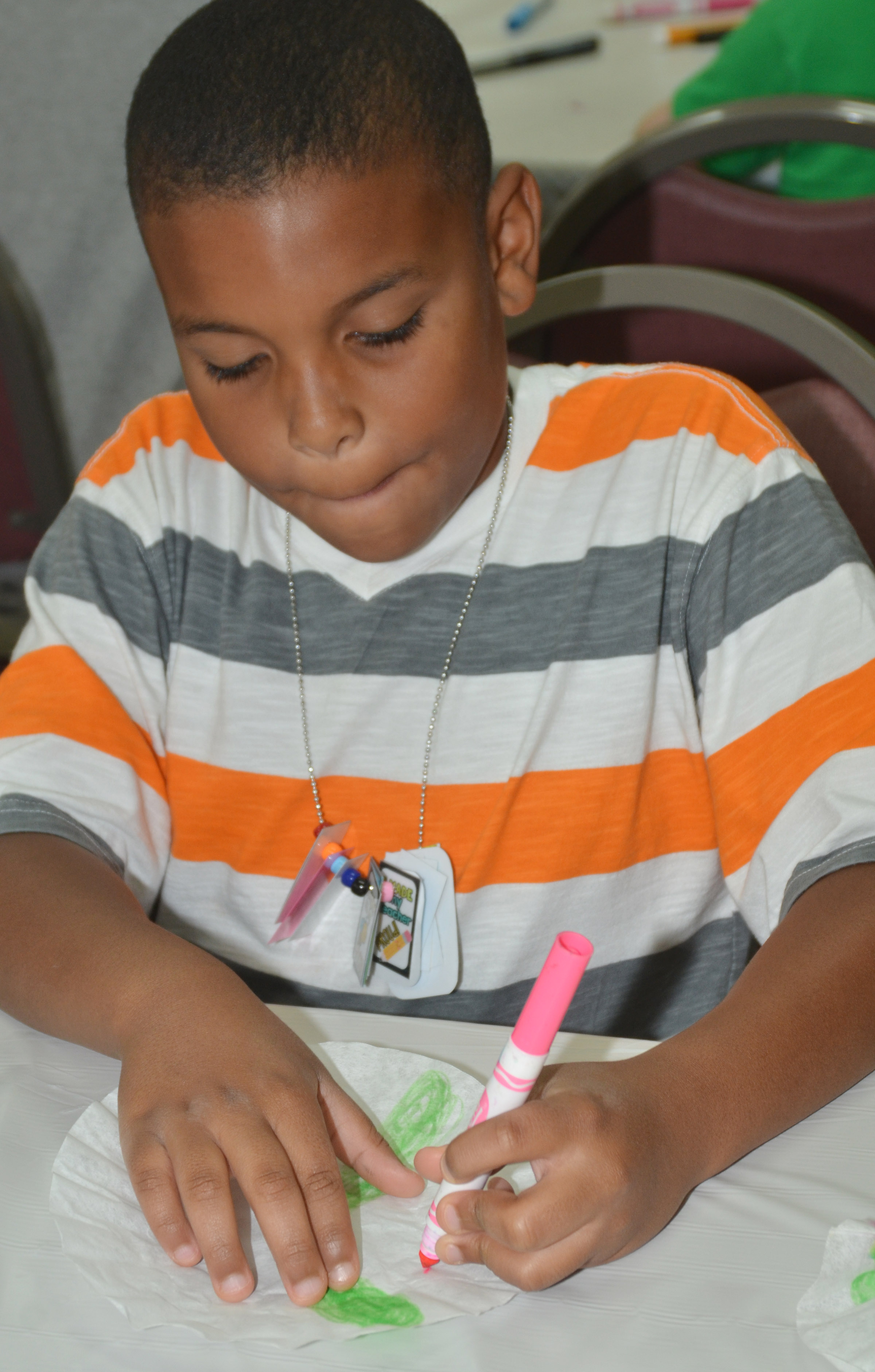 CES second-grader Zaemar Hoskins colors his coffee filter, which will be made into a butterfly.