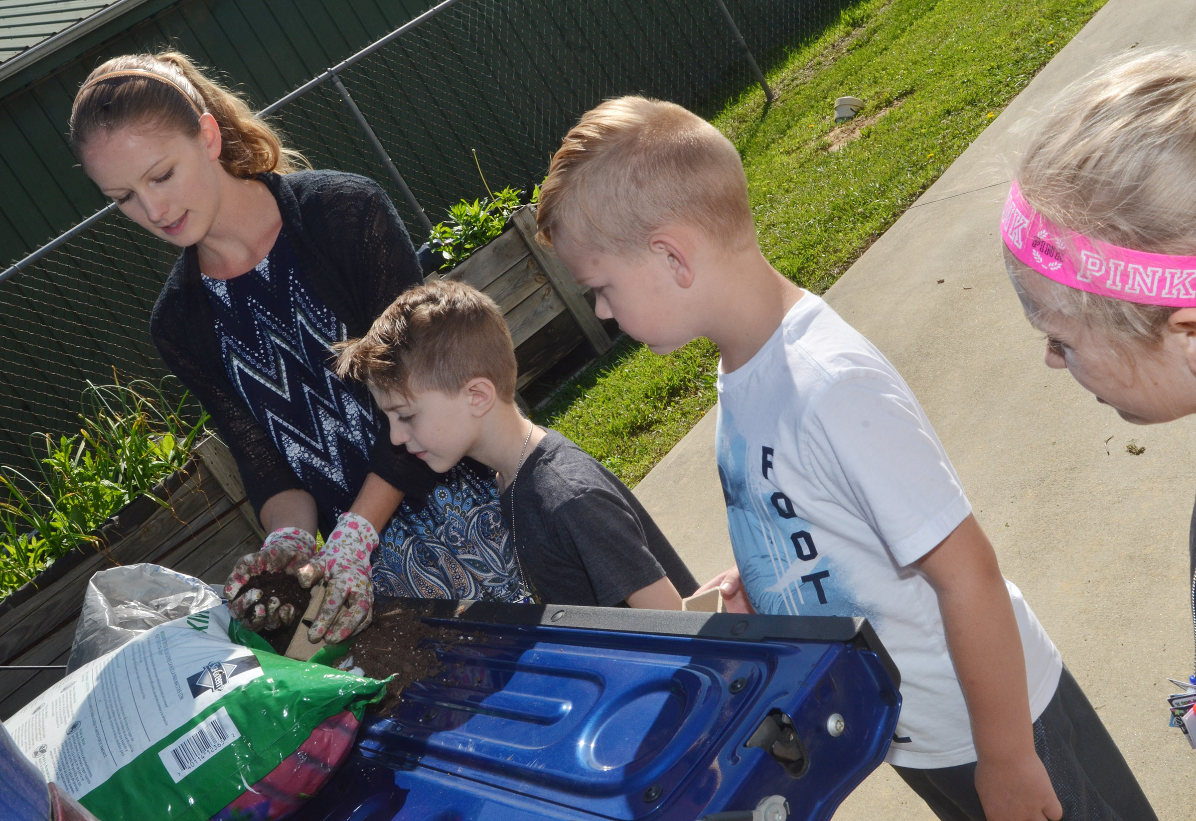 Kara Back, extension agent for horticulture at Taylor County Extension Office, helps CES kindergarteners Caleb Goodson, at left, and John Hagan Newton to plant flowers.
