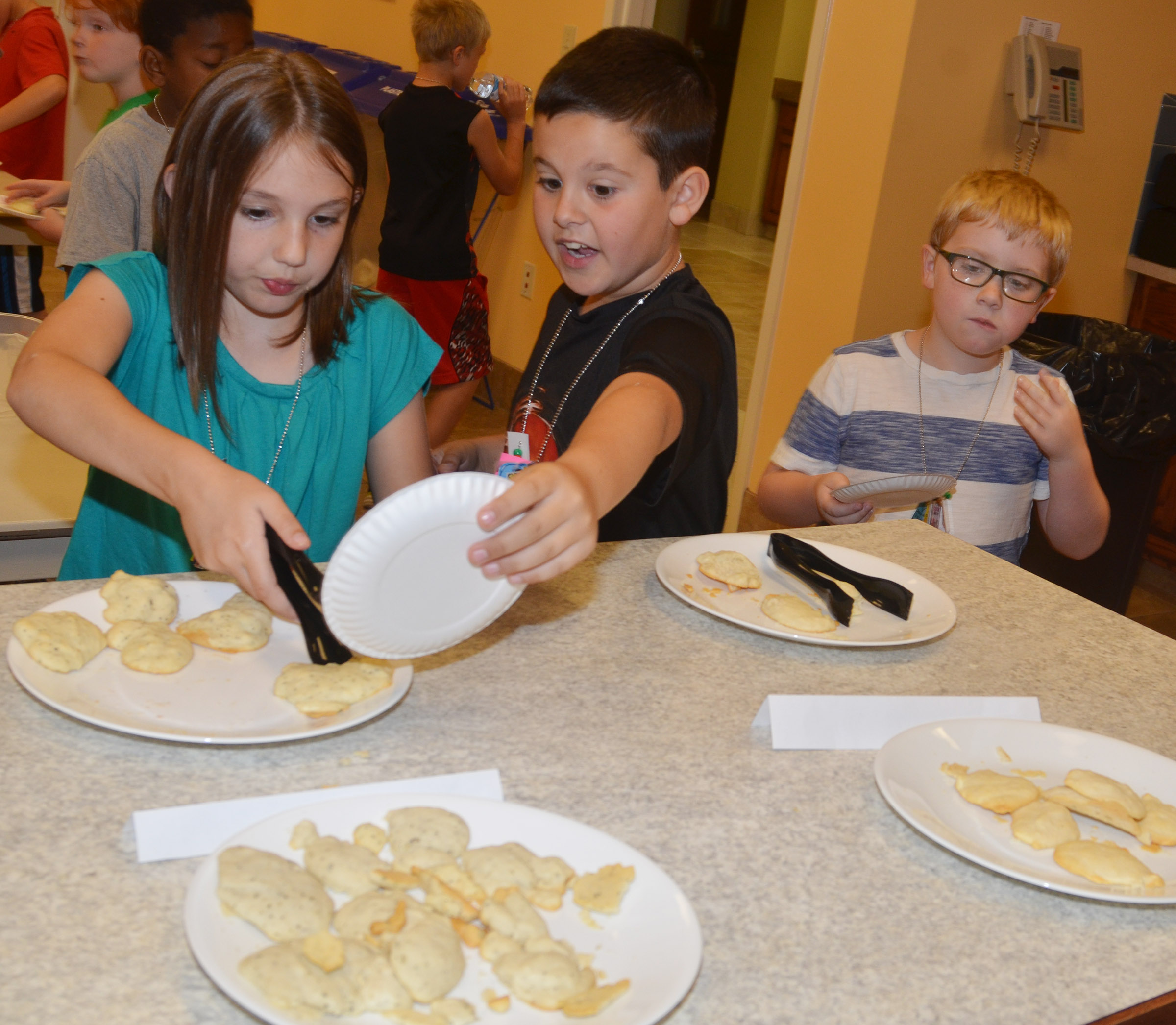 CES second-graders, from left, Kairi Tucker, Damien Clark and Aidan Bowles sample biscuits that they made together.