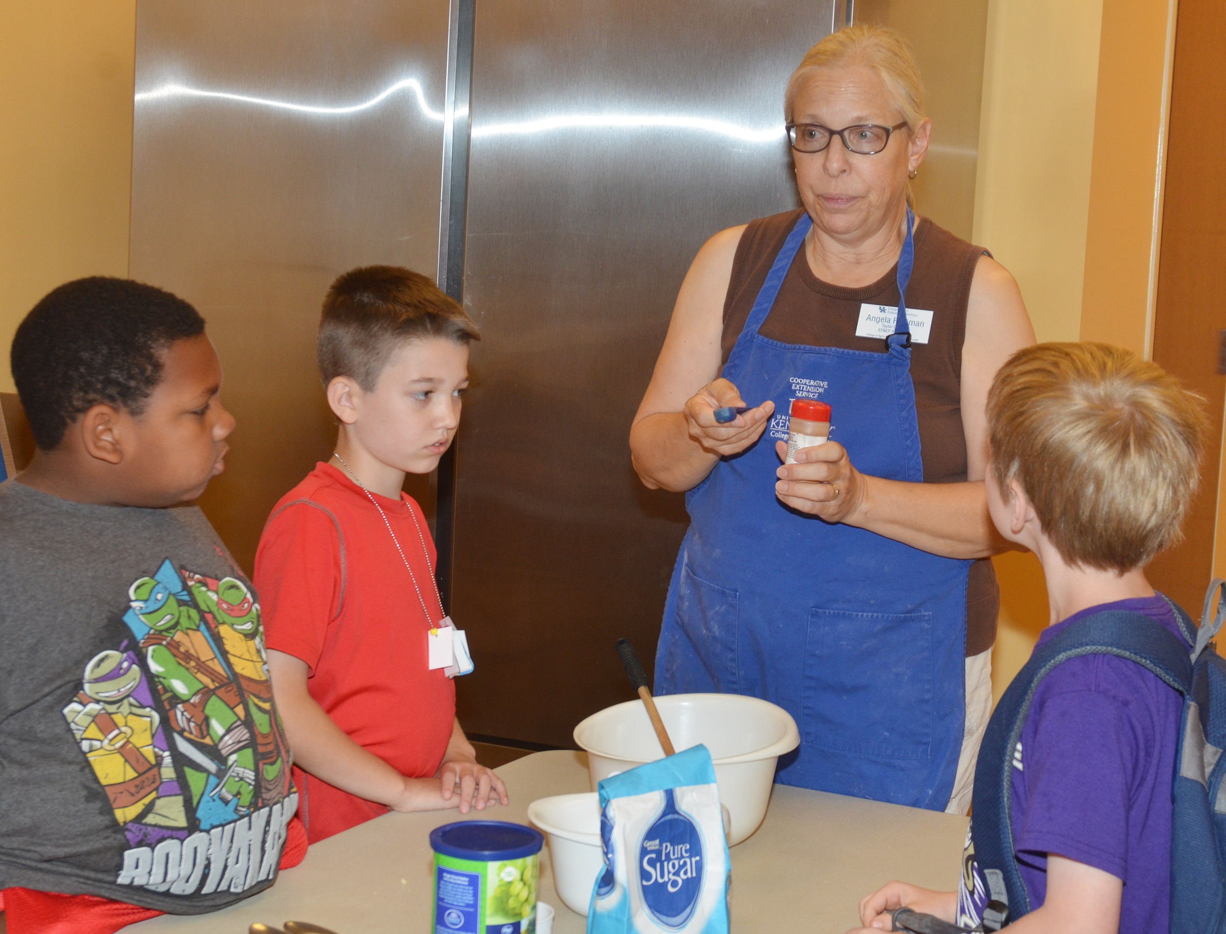 Angie Freeman, expanded foods and nutrition program assistant at Taylor County Extension Office, talks to CES Wings Express students about measuring dry ingredients.