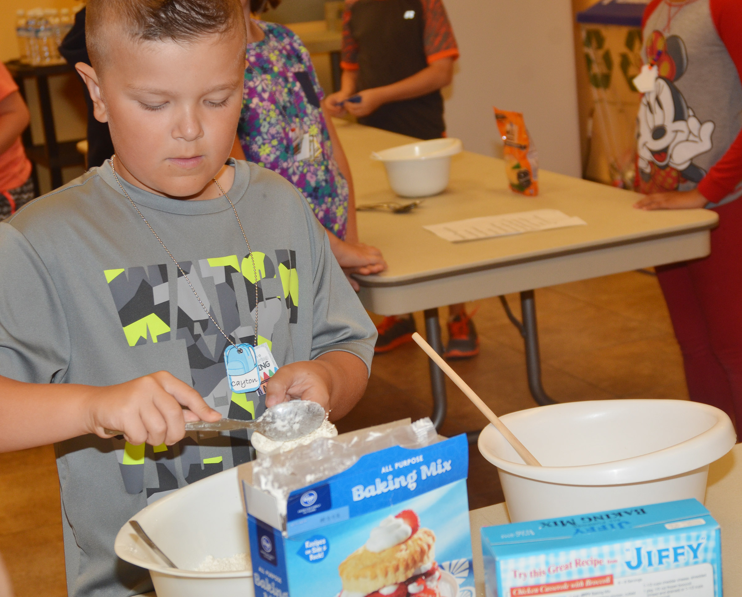 CES second-grader Cayton Lawhorn measures ingredients as he and his group members make biscuits.