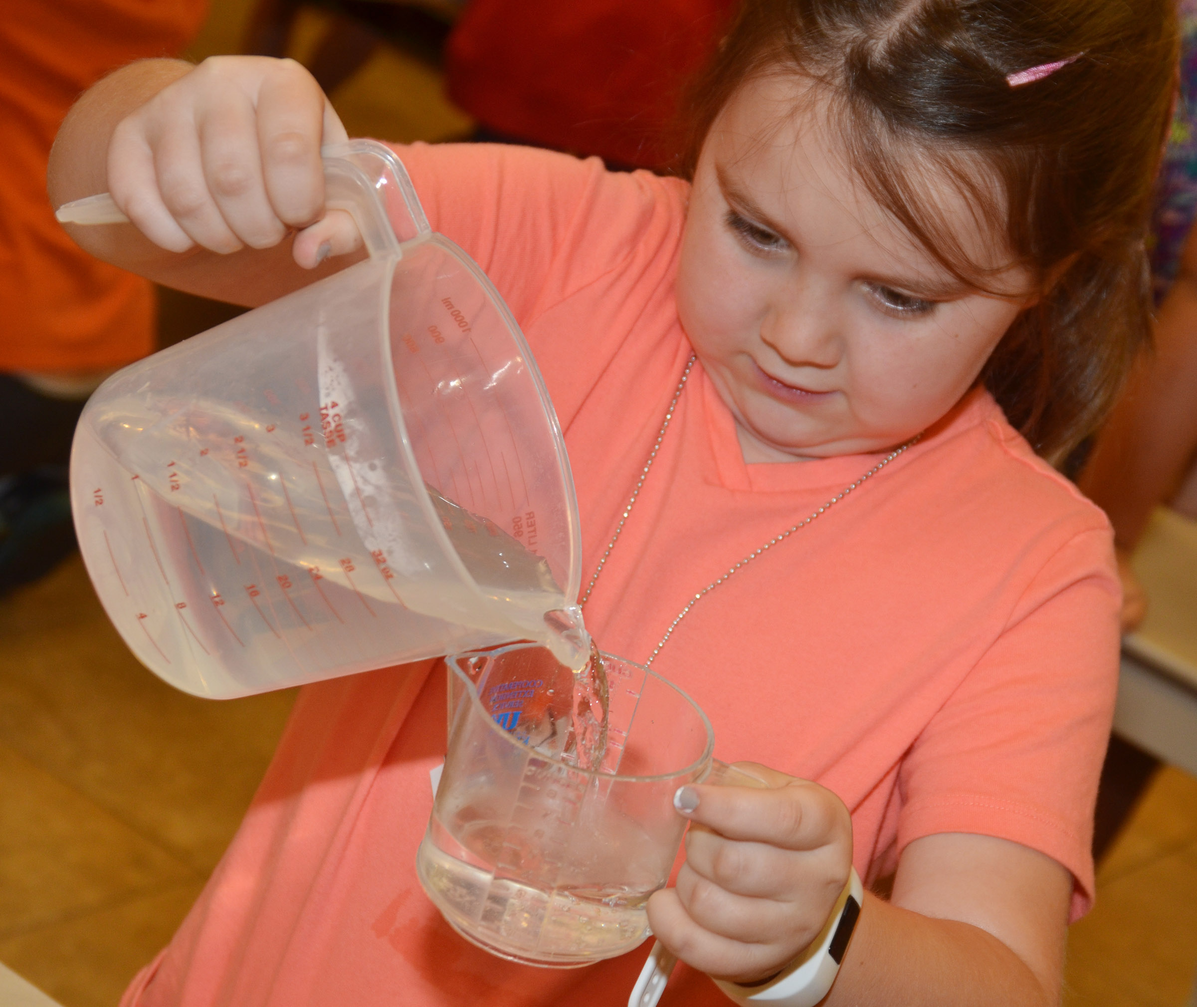 CES third-grader Maylee Wilds measures water as she and her classmates make biscuits.