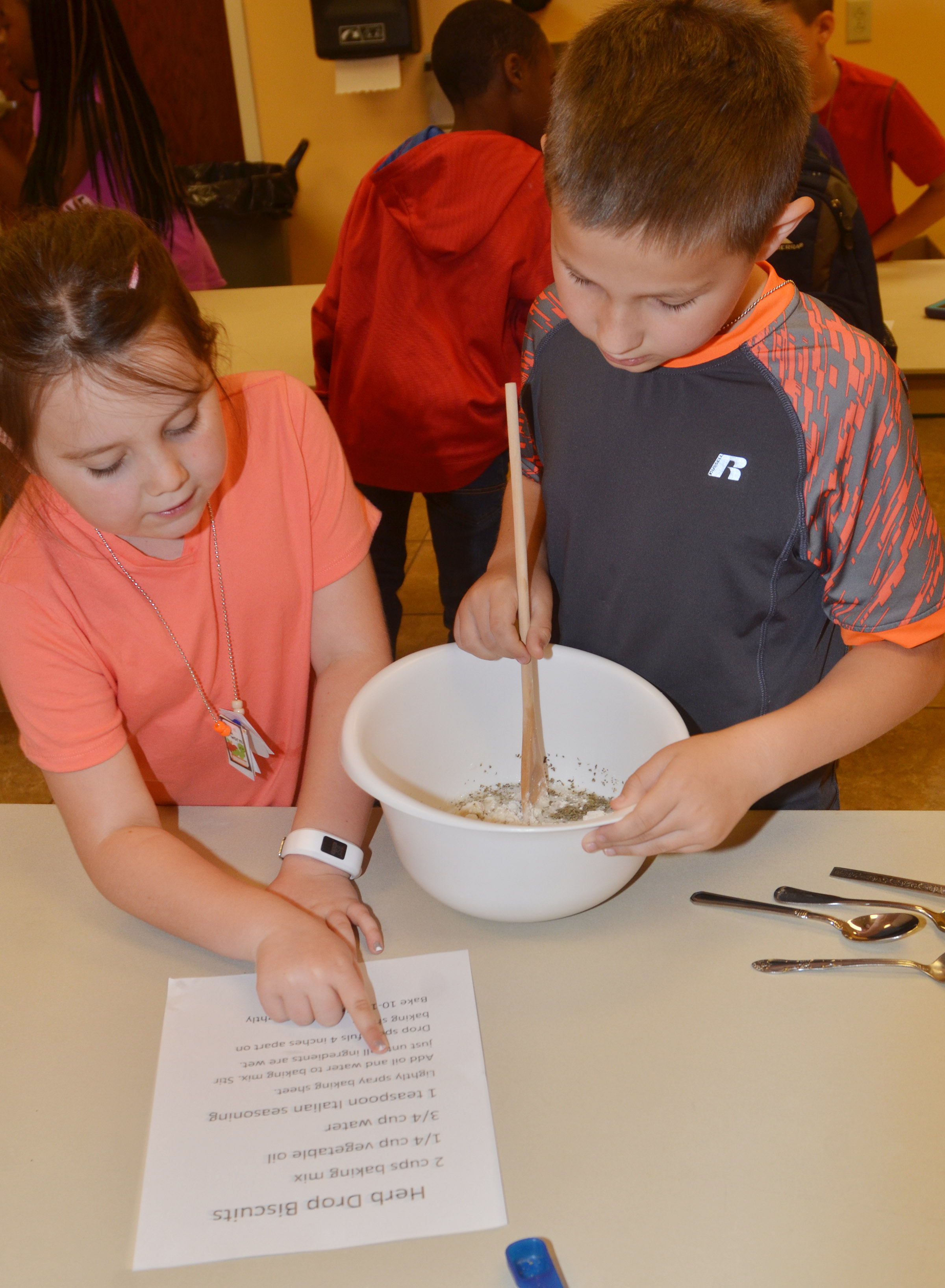 CES third-grader Maylee Wilds, at left, and Grayson Dooley follow a recipe as they make biscuits.