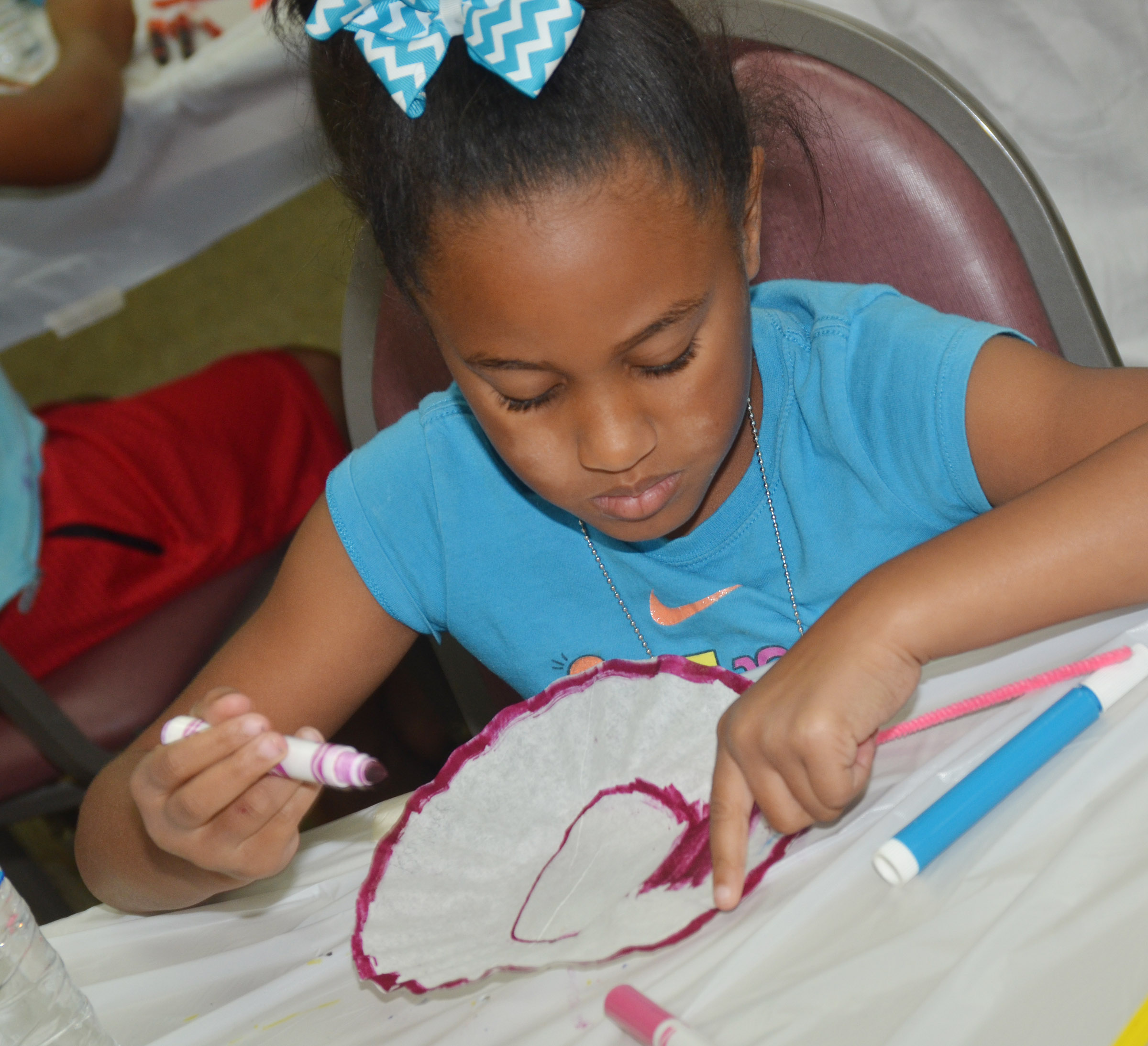 CES first-grader Kadance Ford colors her coffee filter, which will be made into a butterfly.