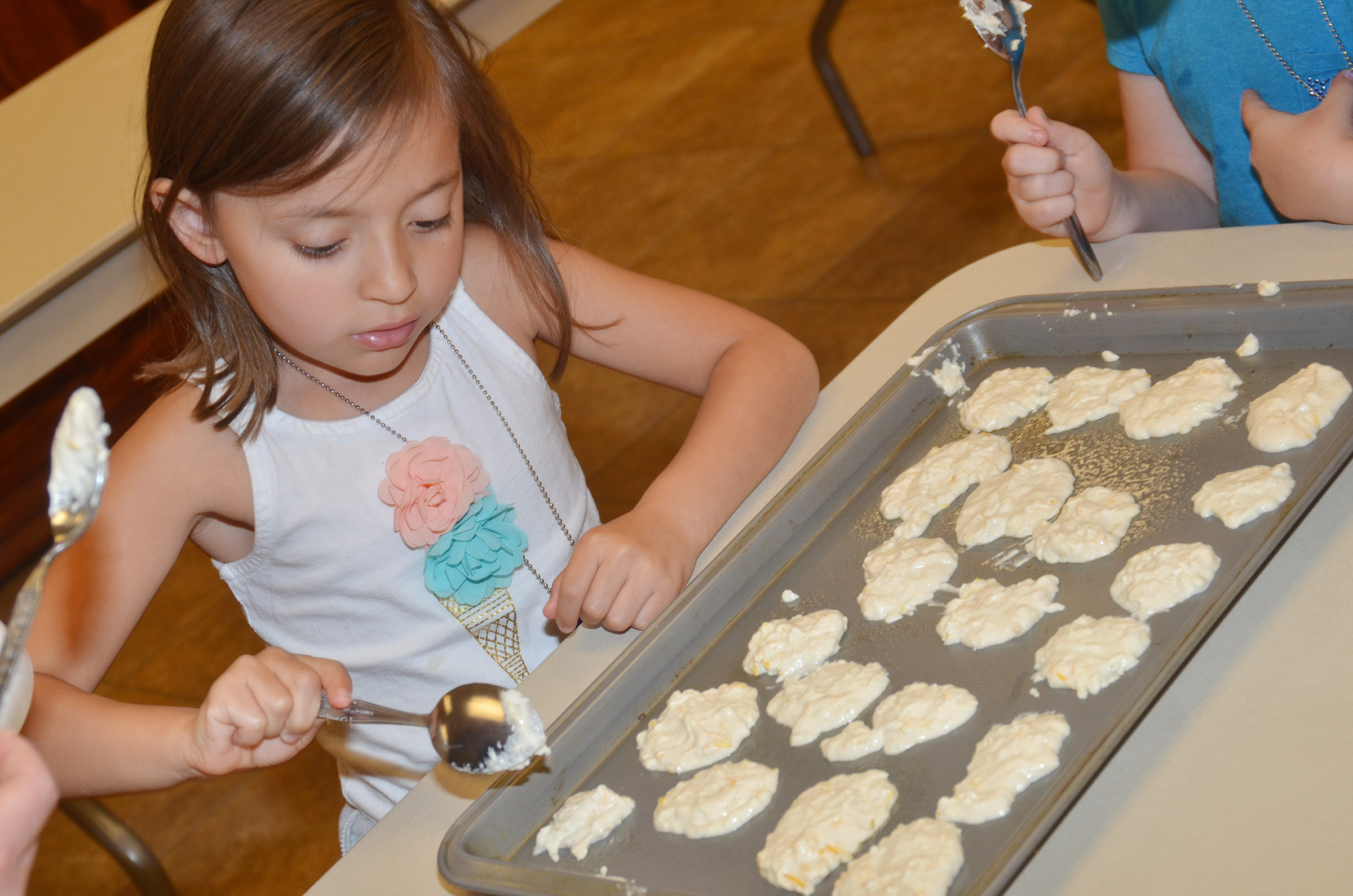 CES kindergartener Gabriella Tate dips biscuit mix on a baking sheet.