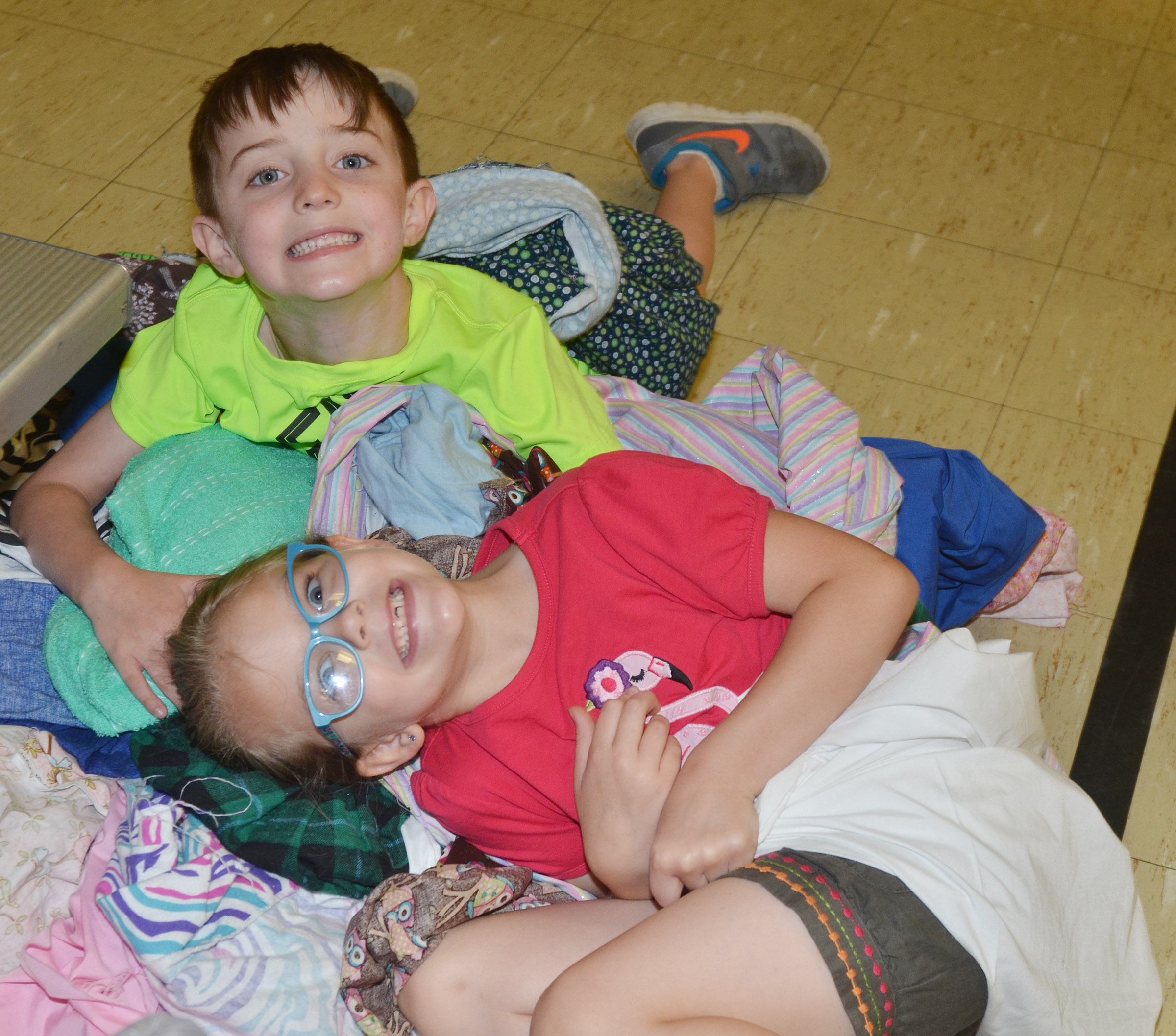 CES kindergarteners Caleb Goodson and Zoe Weddle get comfortable in a pile of bedsheets as they get set to read together.