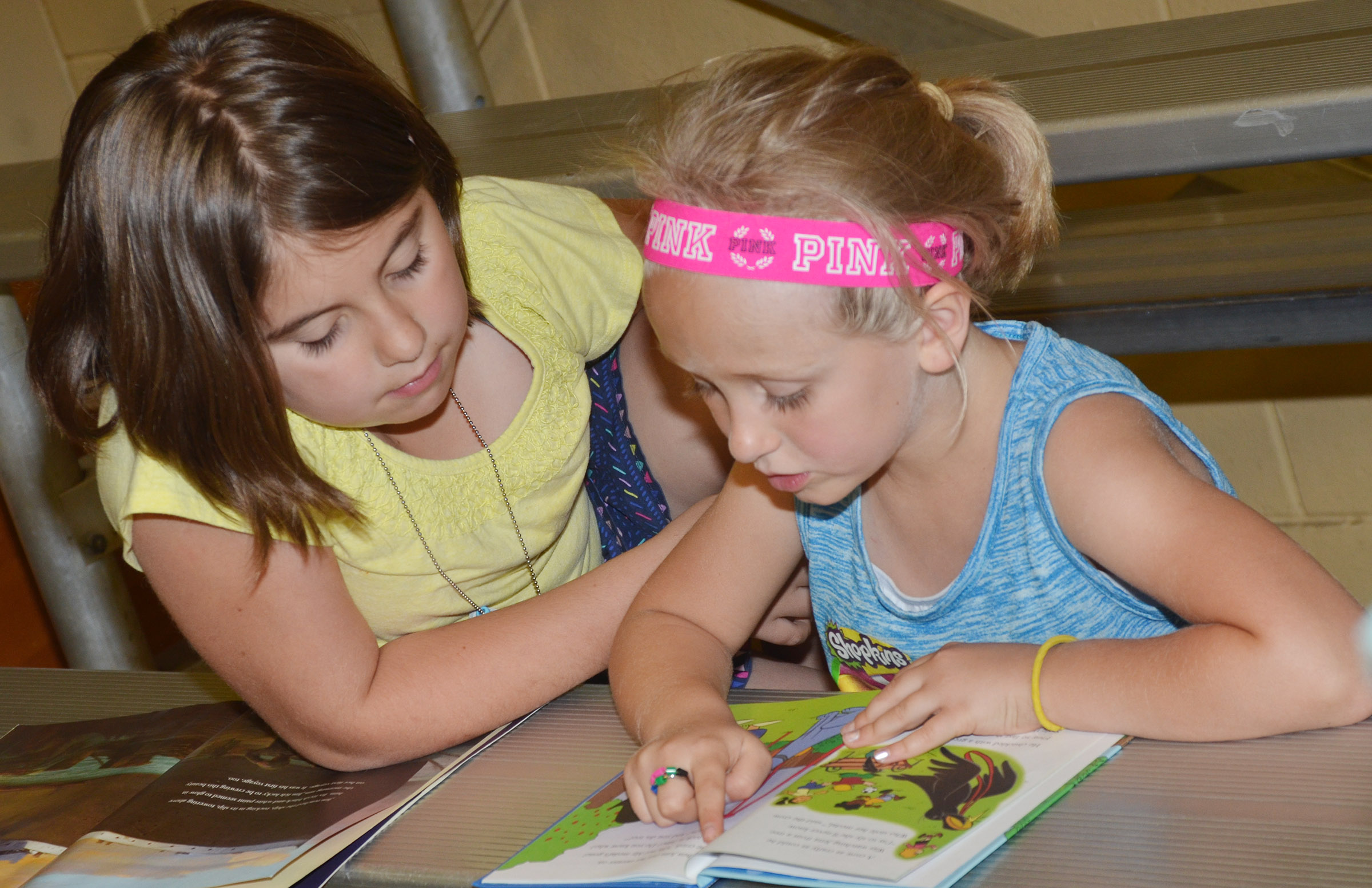 CES third-grader Adrianna Garvin, at left, reads with her sister, kindergartener LeeAnna Garvin.