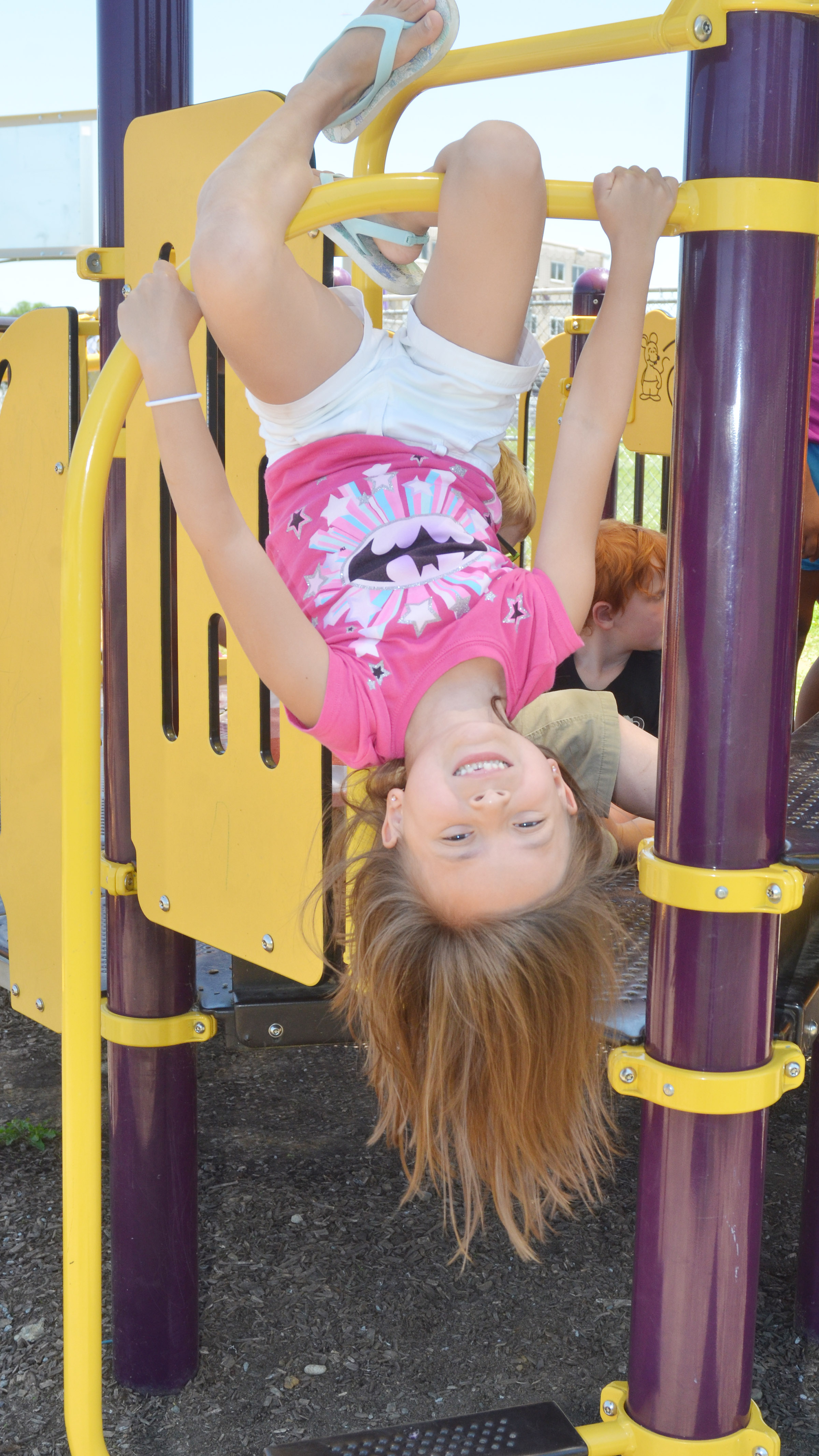 CES kindergartener Gabriella Tate hangs upside down while playing on the playground.
