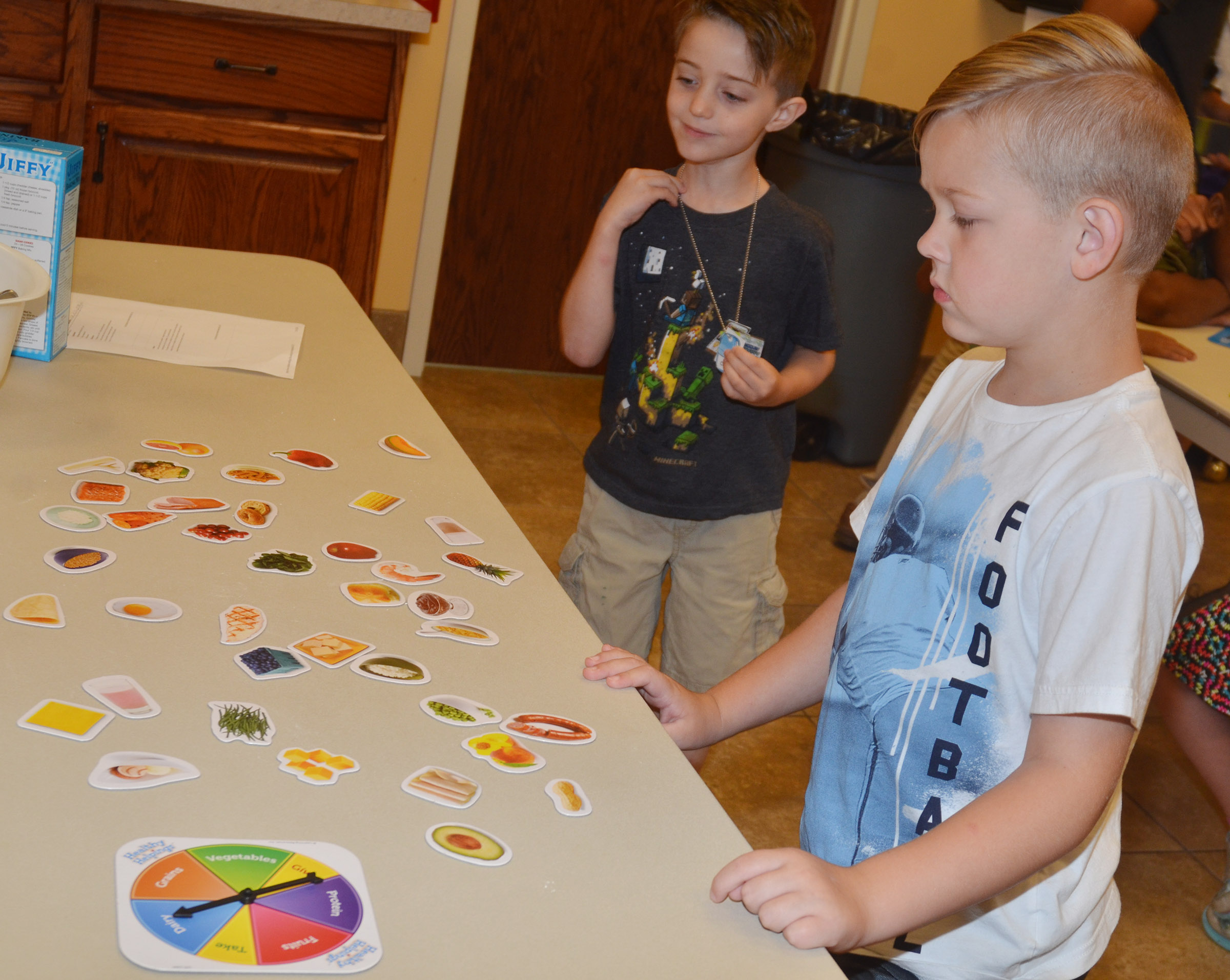 CES kindergarteners Caleb Goodson, at left, and John Hagan Newton play a food group game.