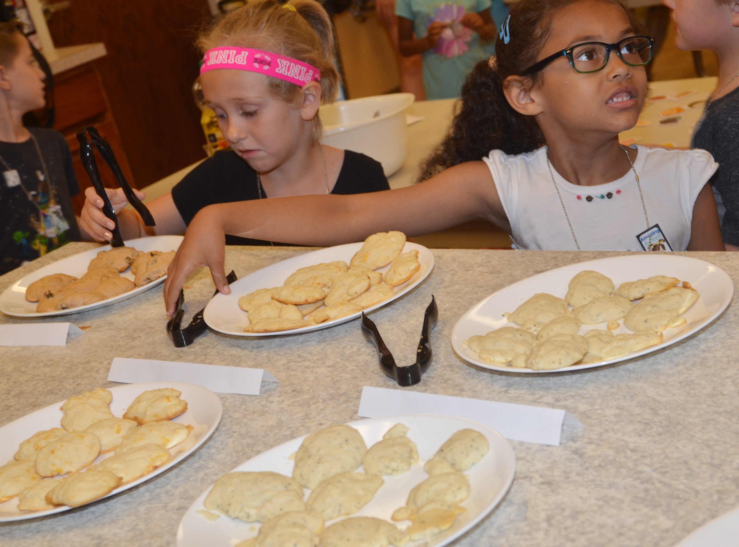 CES kindergarteners LeeAnna Garvin, at left, and Marlee Dickens sample the biscuits they made with their classmates.