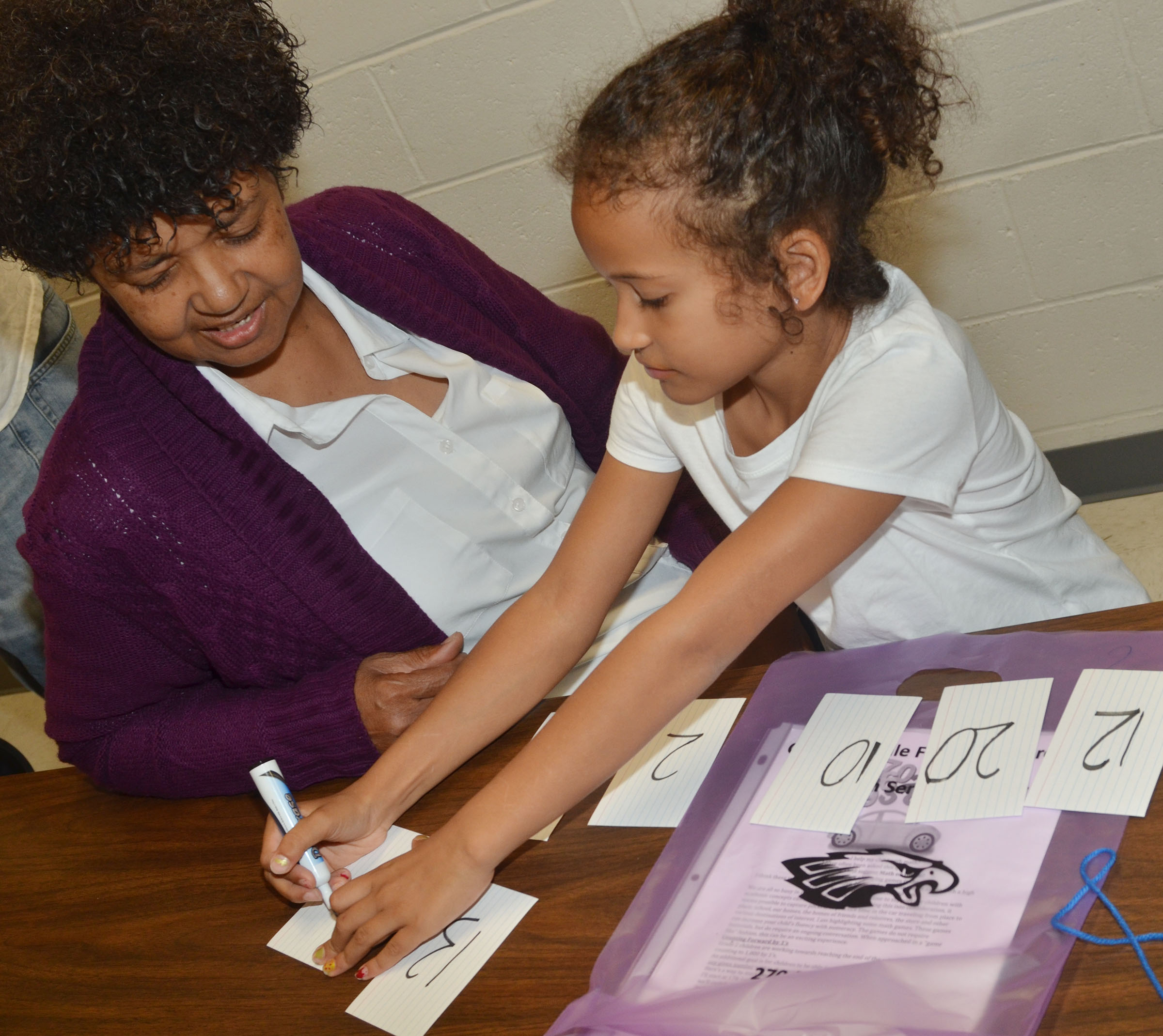 CES second-grader Yazlyn Sutton plays a math game with her grandmother, Peggy Taylor.