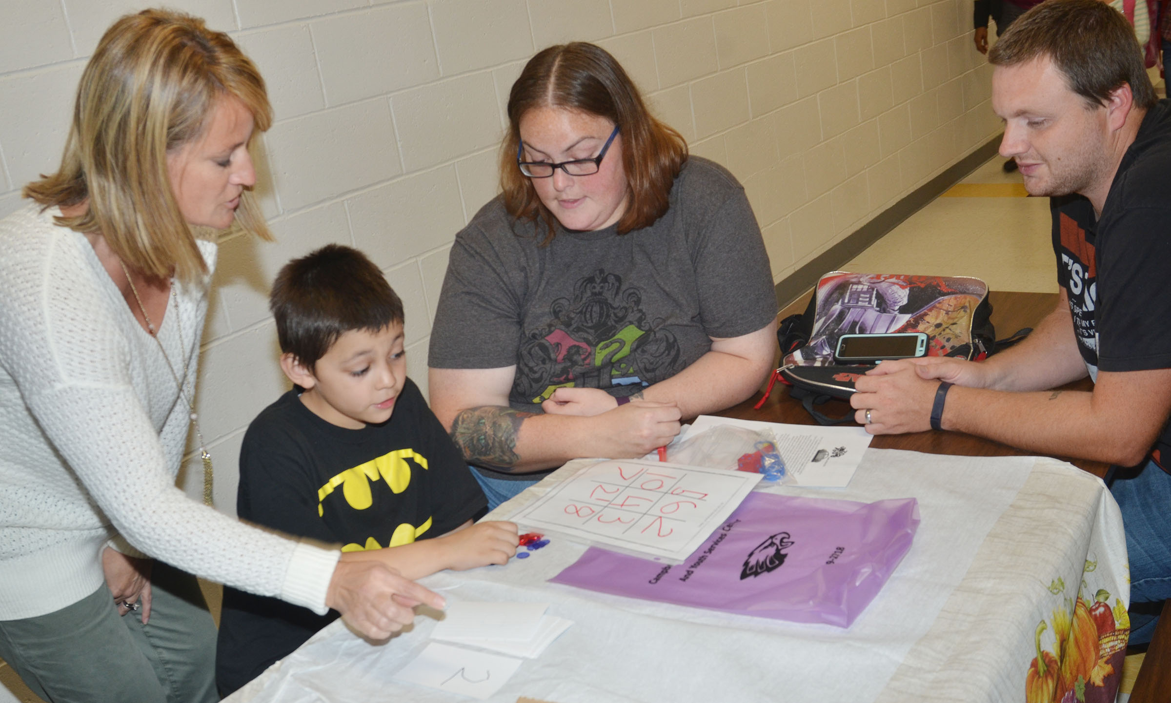 CES kindergartener Keagan Shearer plays a math game with his parents, Addie and Ben, and CES teacher Vanessa Adkins, at left.