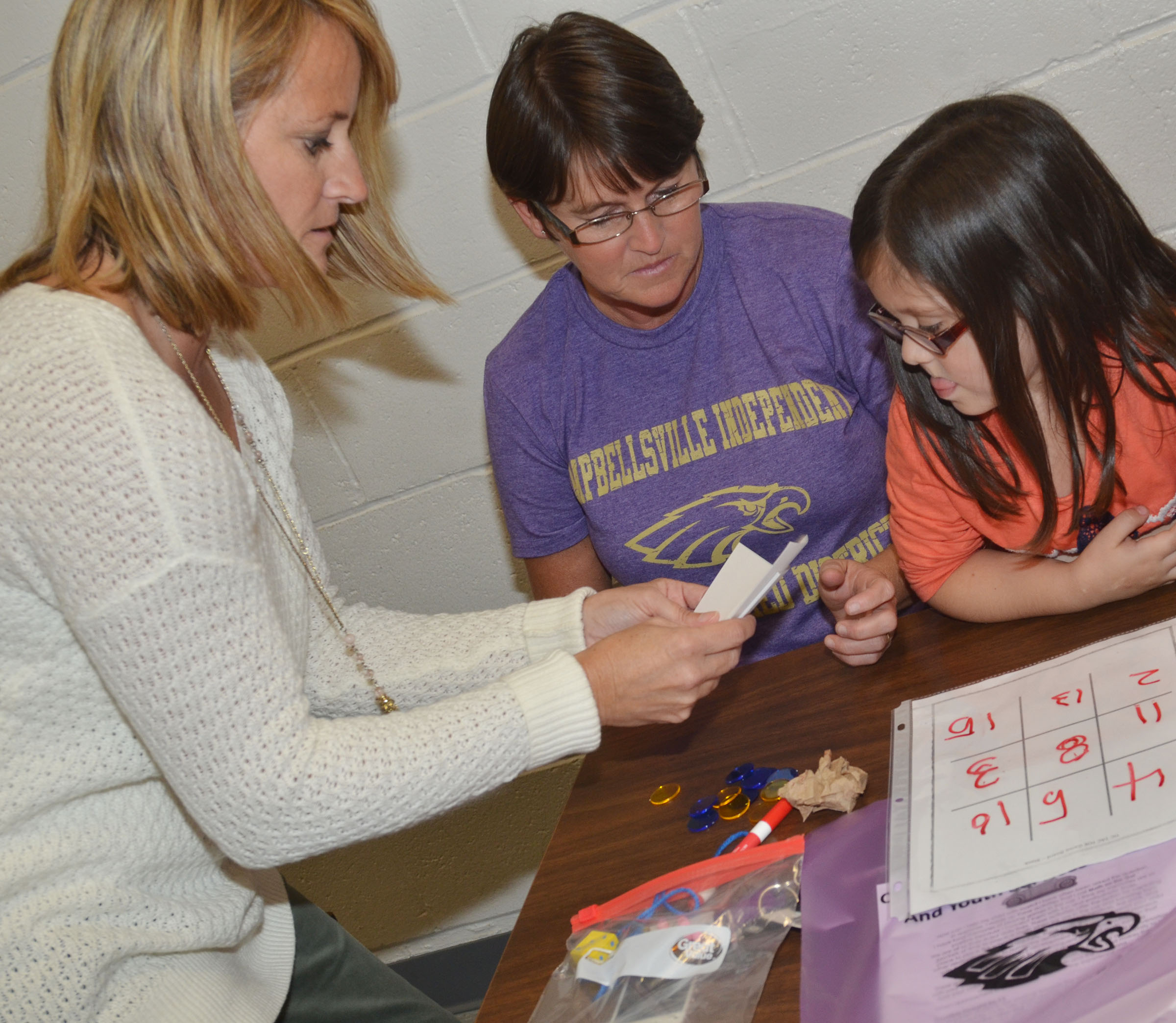 CES kindergartener Trinity Clark plays a math game with her grandmother, Bobbi Faulkner, and CES math teacher Vanessa Adkins.
