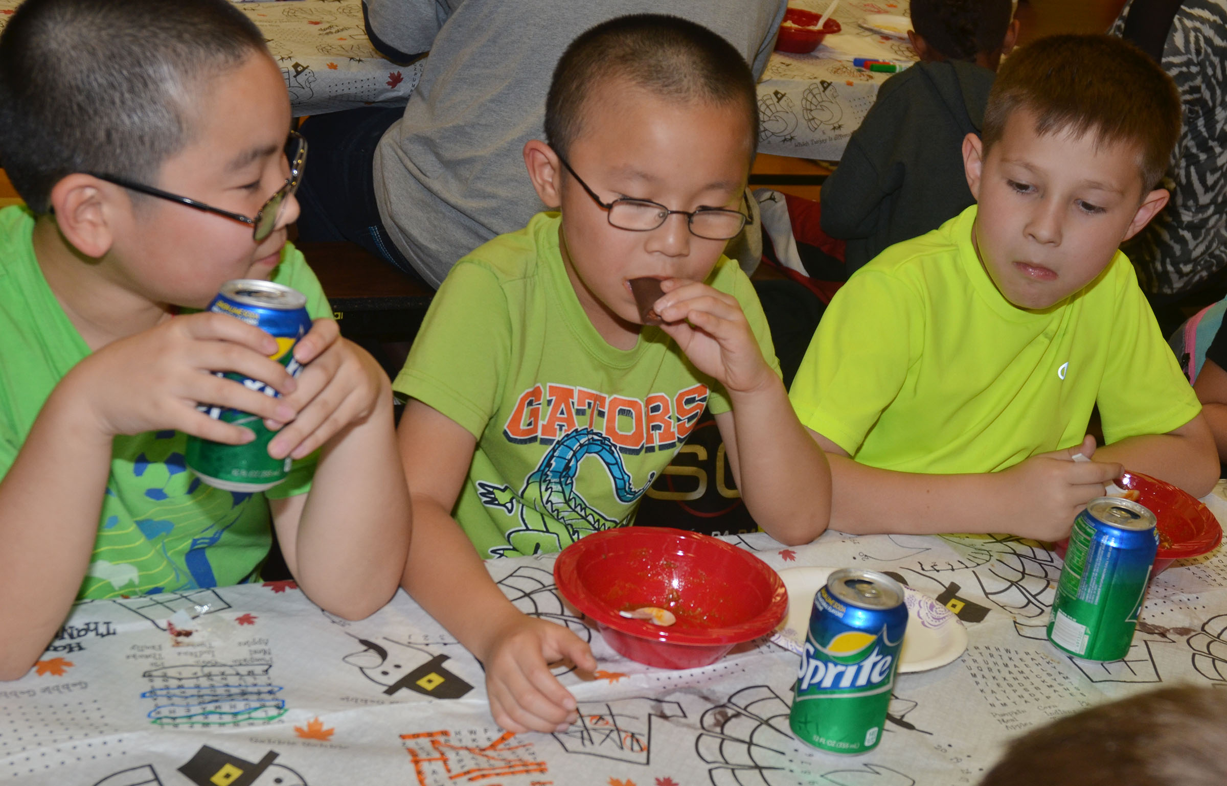 From left, CES third-grader Martin Yang, second-grader Alex Yang and third-grader Grayson Dooley eat chili together.