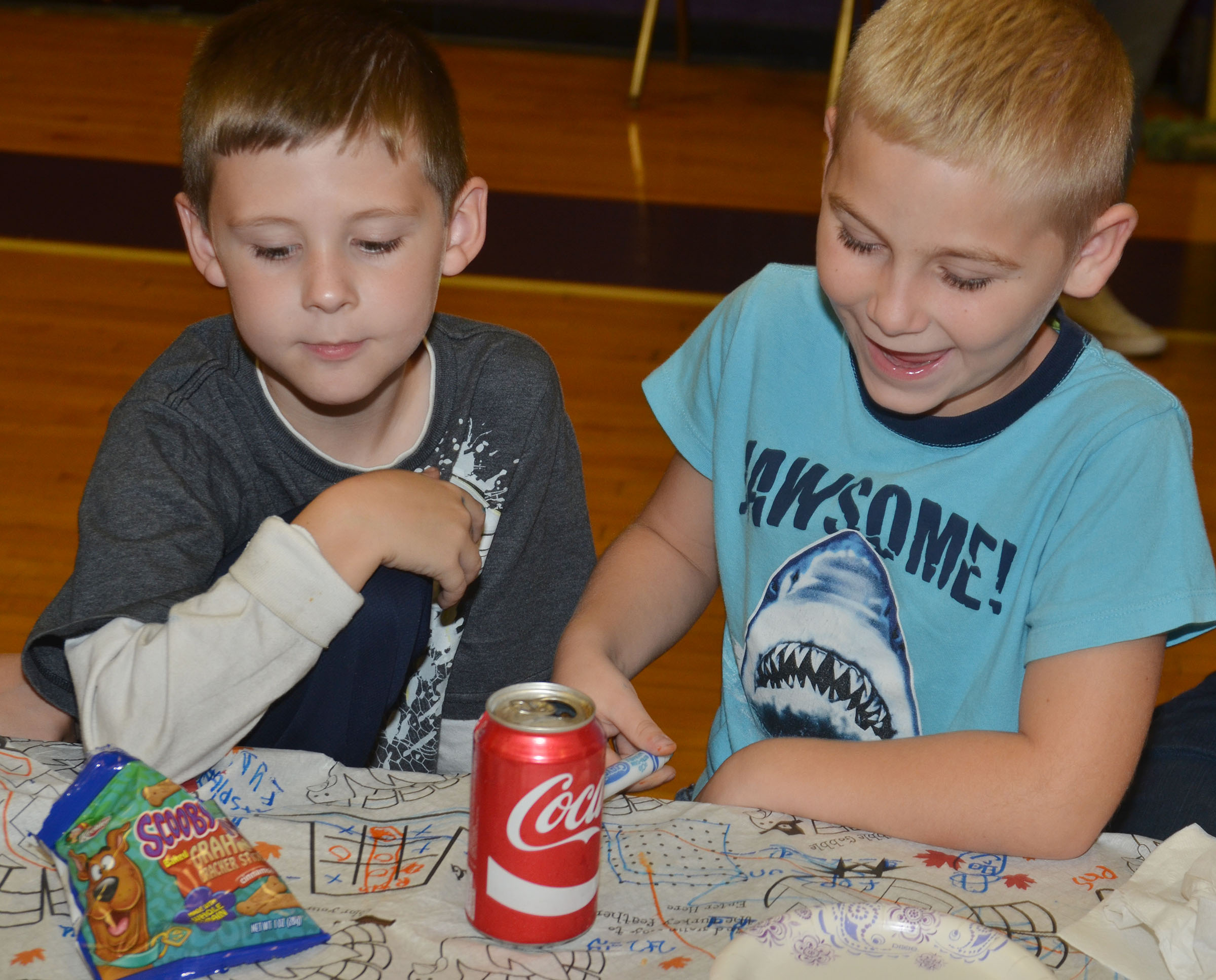 CES second-graders Ryan Tungate, at left, and Joseph Greer color and play games together.