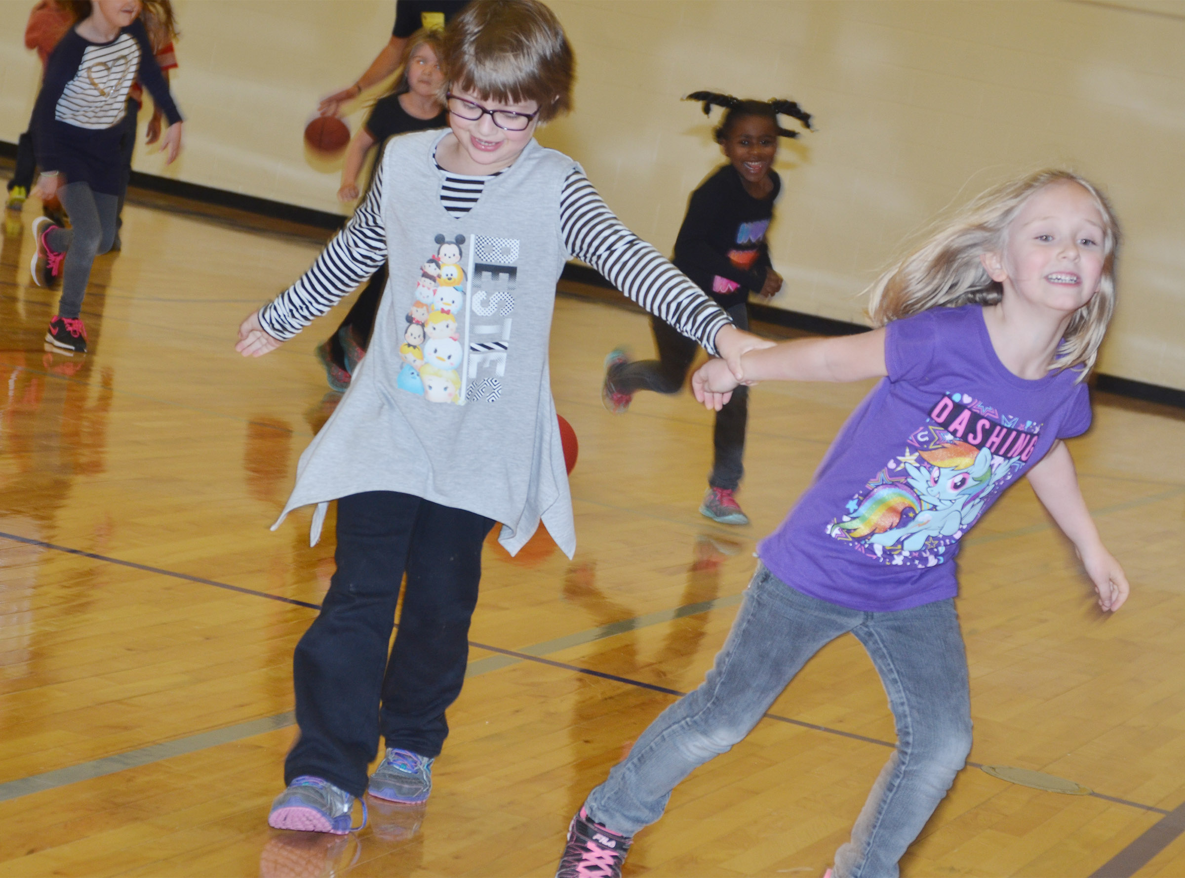 CES first-grader Addelyn Dooley, at left, and kindergartener LeeAnna Garvin run in the gym.
