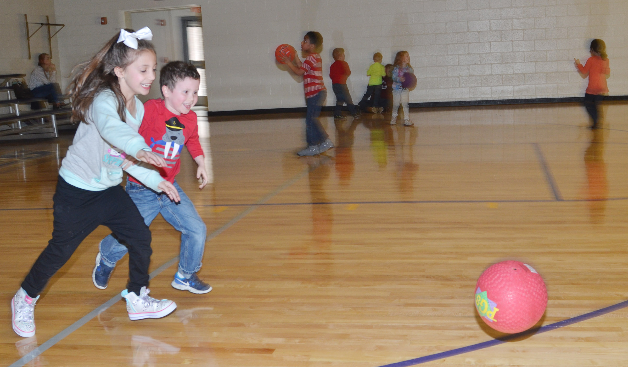 CES first-grader Lillian Martin, at left, and kindergartener Brayden Perkins run for the kickball.