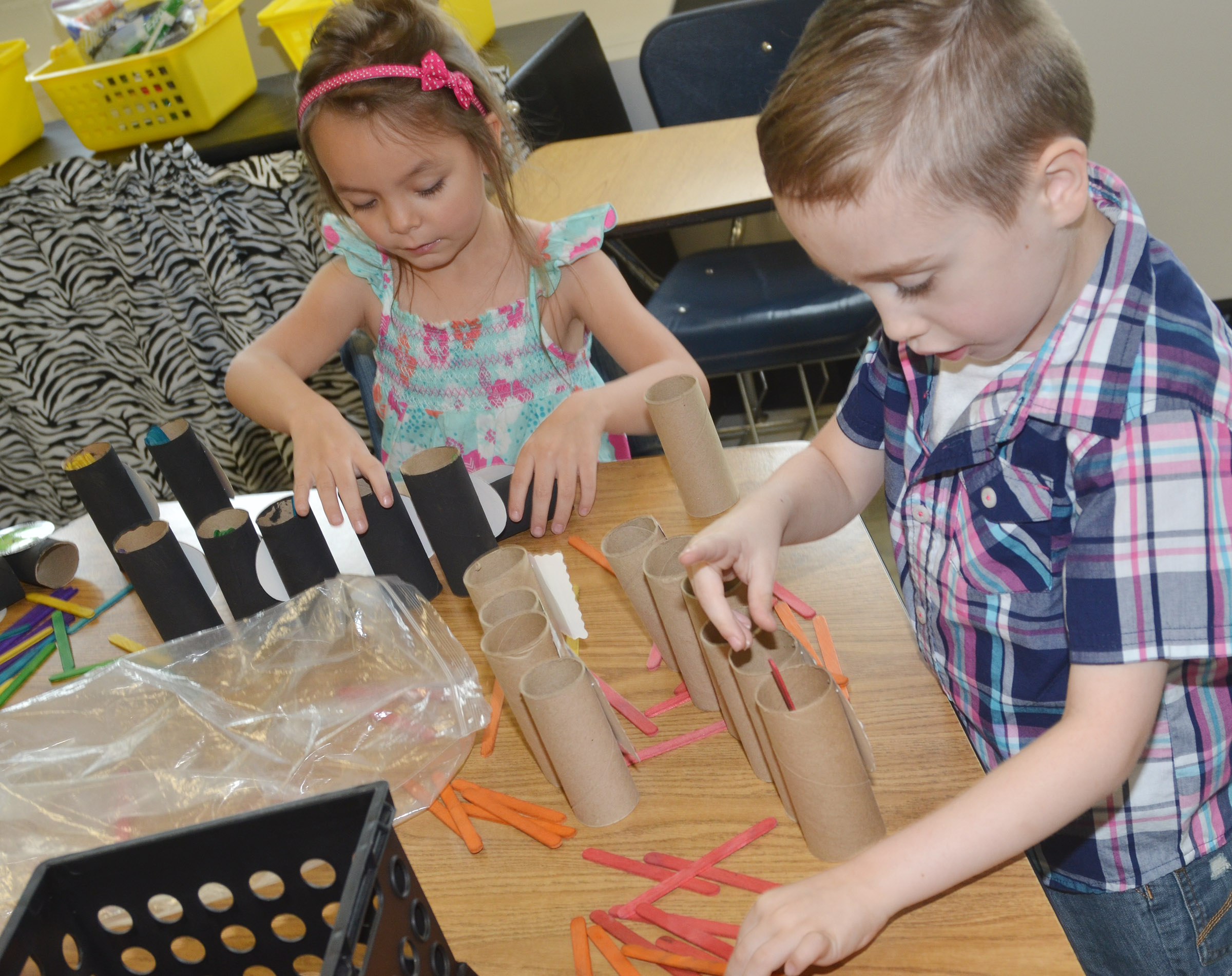 CES kindergarteners Kalie Pilkington, at left, and Joshua Dickens count by using sticks and cardboard tubes.