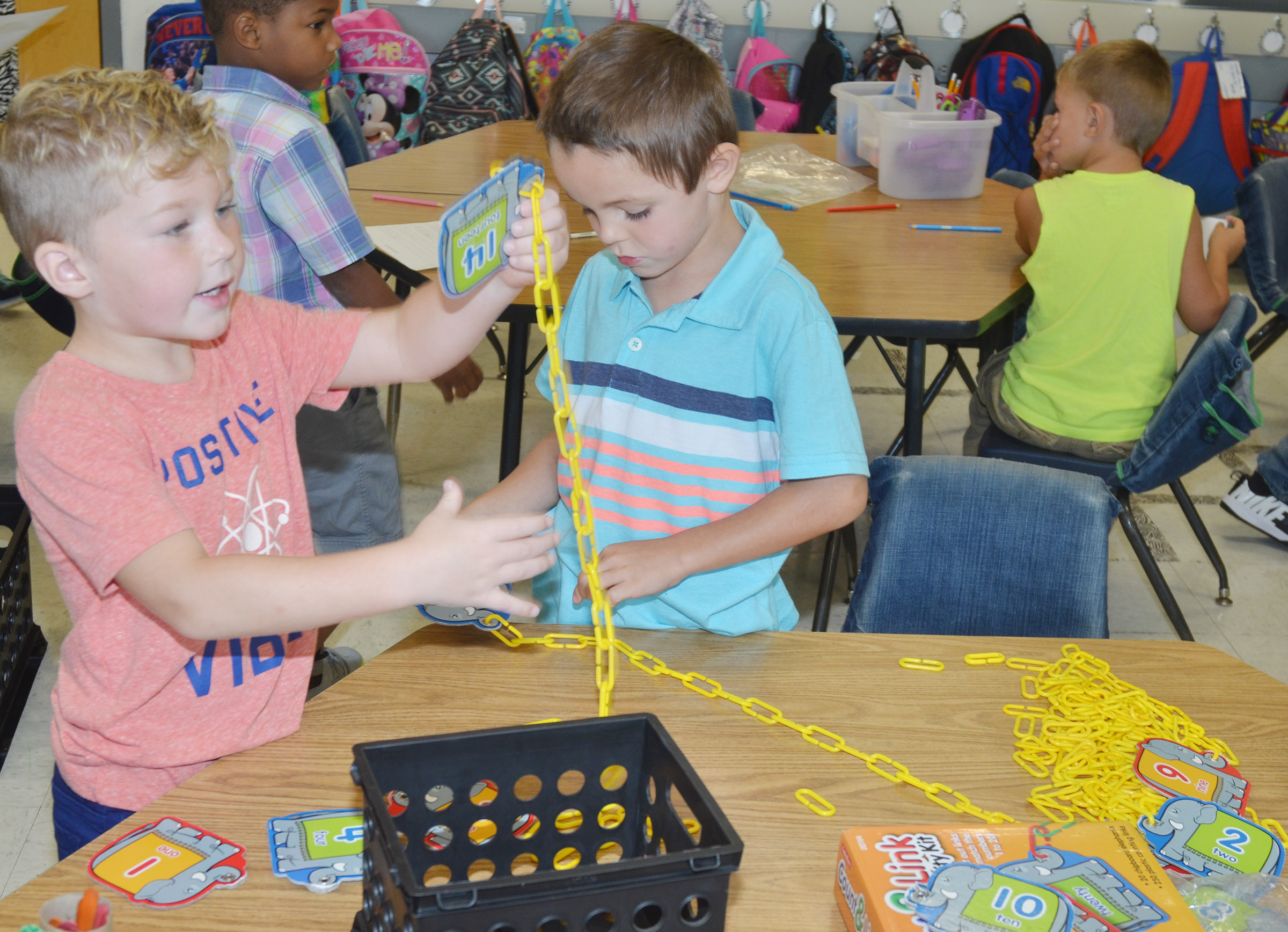 CES kindergarteners Landry Brown, at left, and Hayden Goff count by making a chain of links.