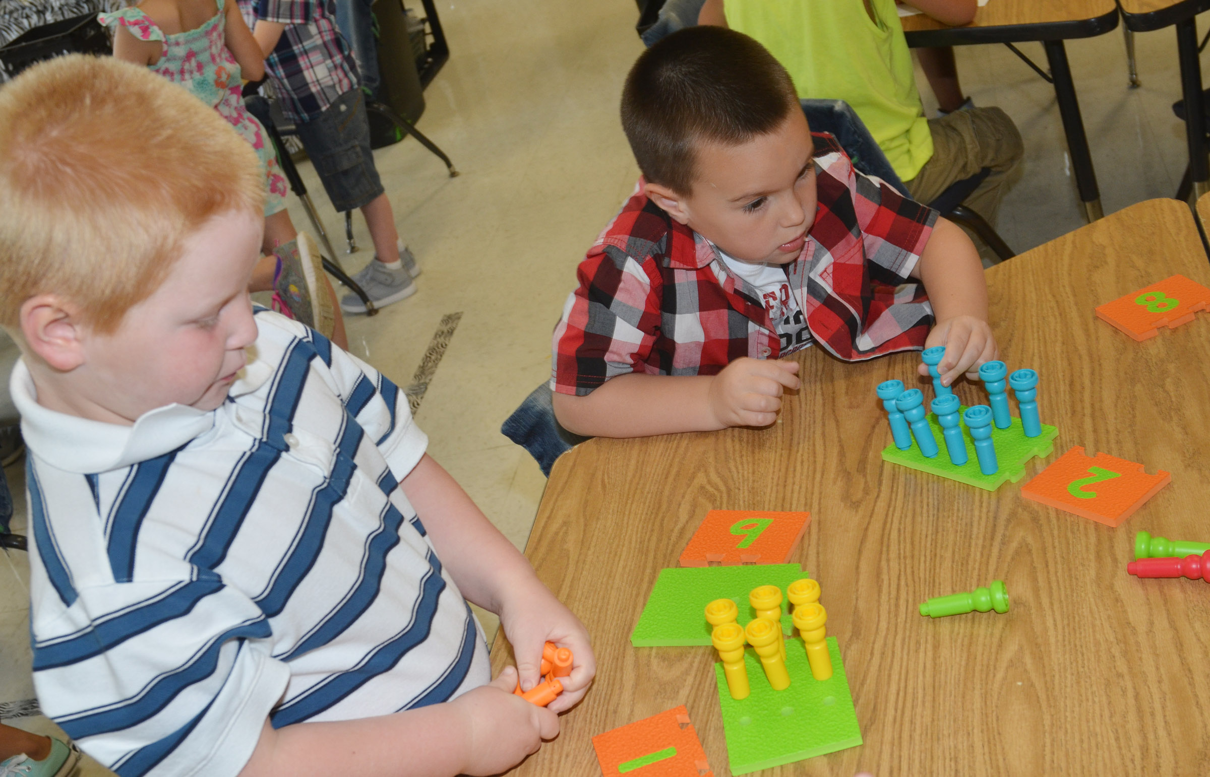 CES kindergarteners Konnar Hicks, at left, and Xander Britton count with pegs.