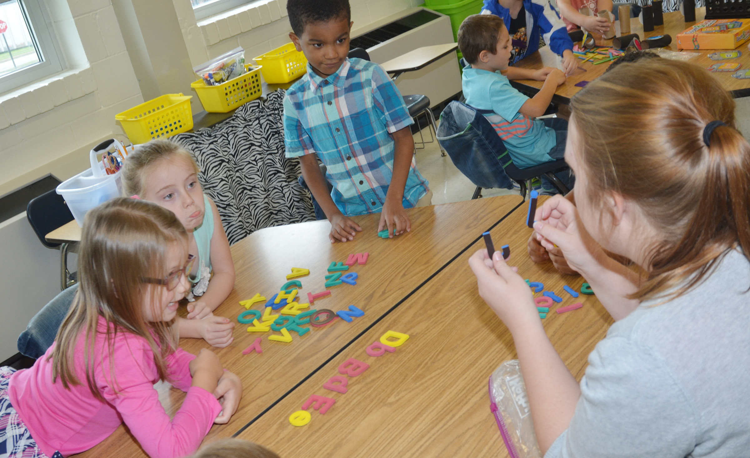 CES student teacher Melissa Langstaff helps kindergarteners, from left, Emmaline Vespie, Courtney Gilbert and Donavon Bell pair uppercase numbers with their lowercase partners.