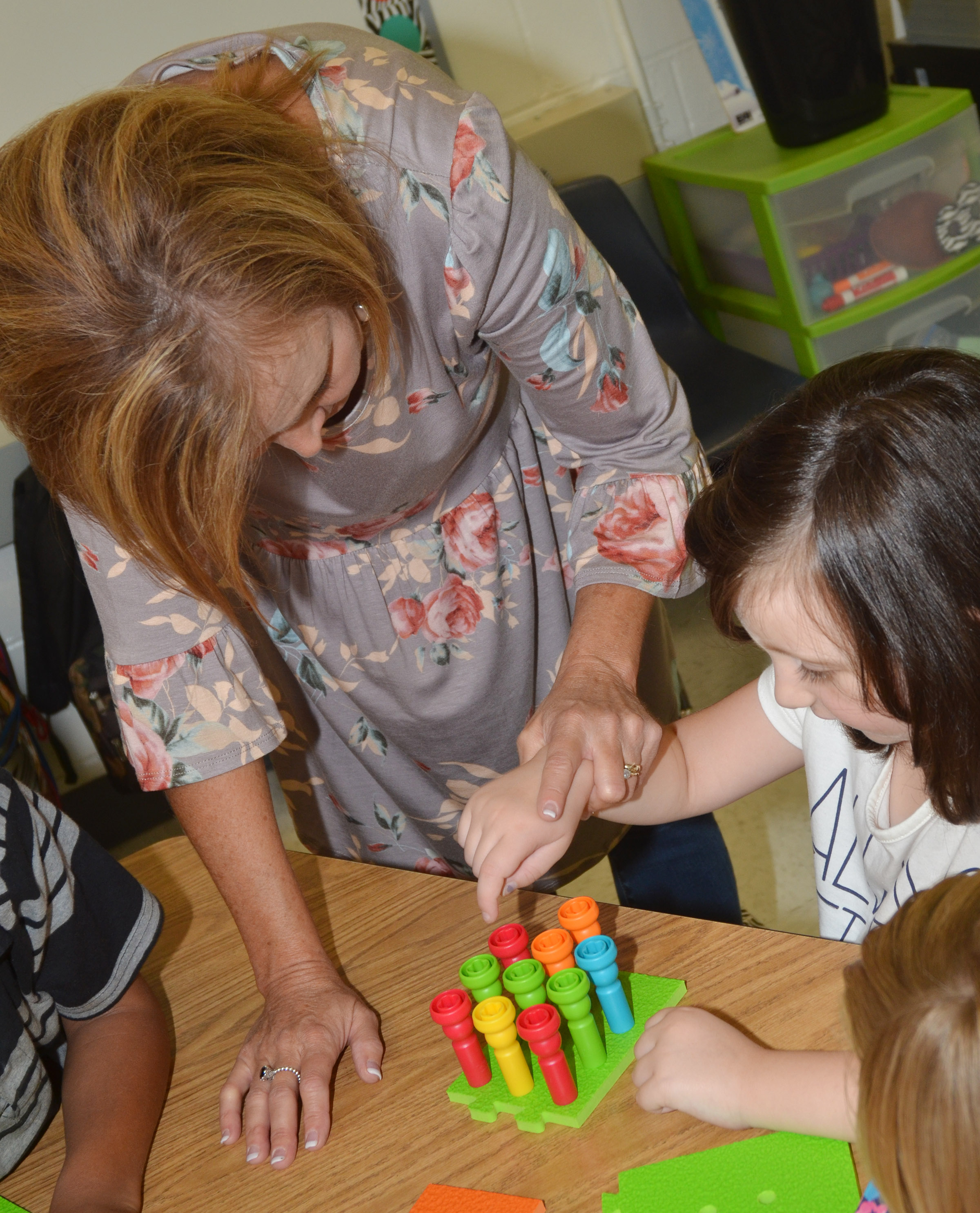 CES kindergarten teacher Lisa Wiseman helps student Abigail Smith count with pegs.