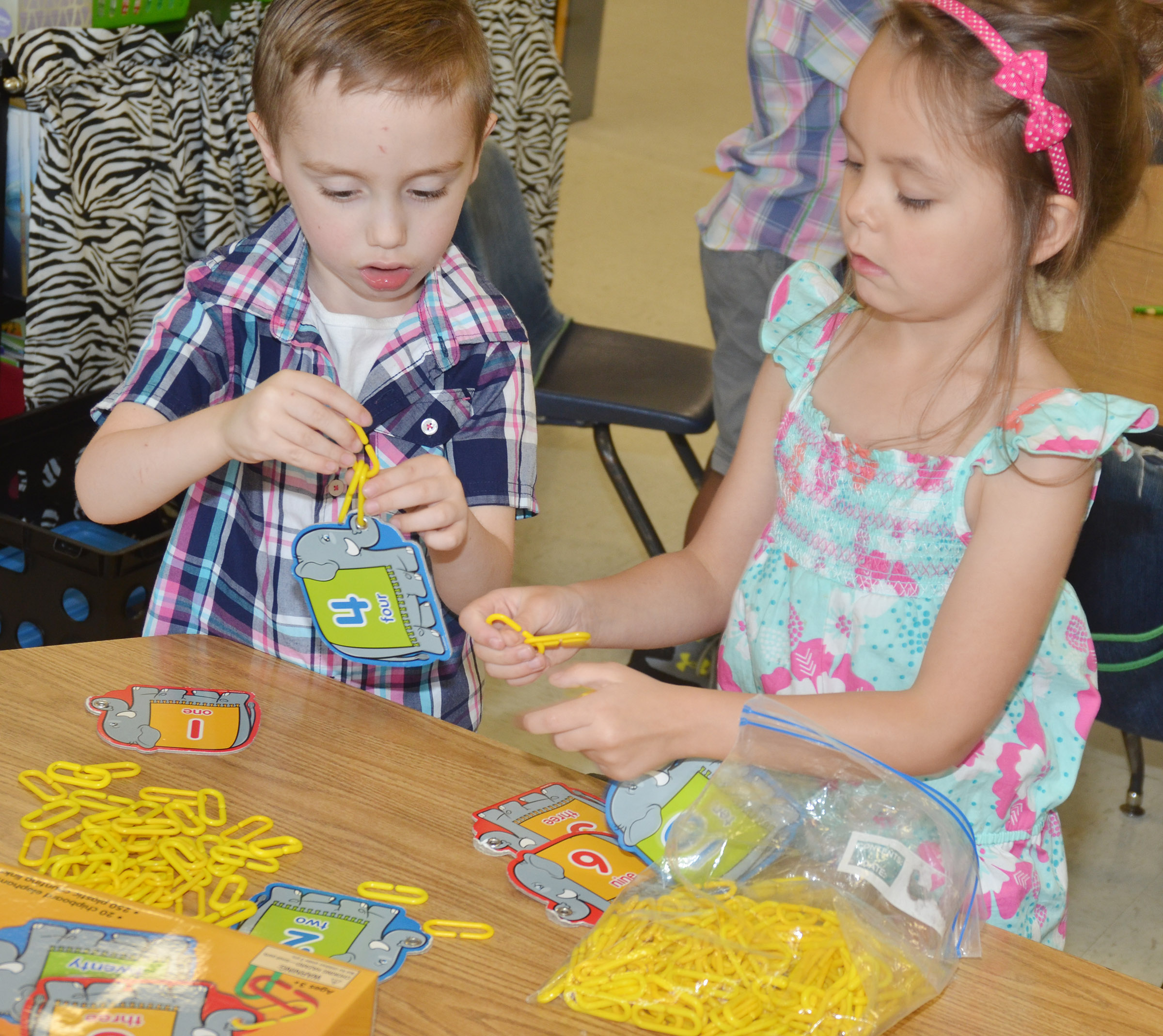 CES kindergarteners Joshua Dickens, at left, and Kalie Pilkington practice counting by making a chain of links.