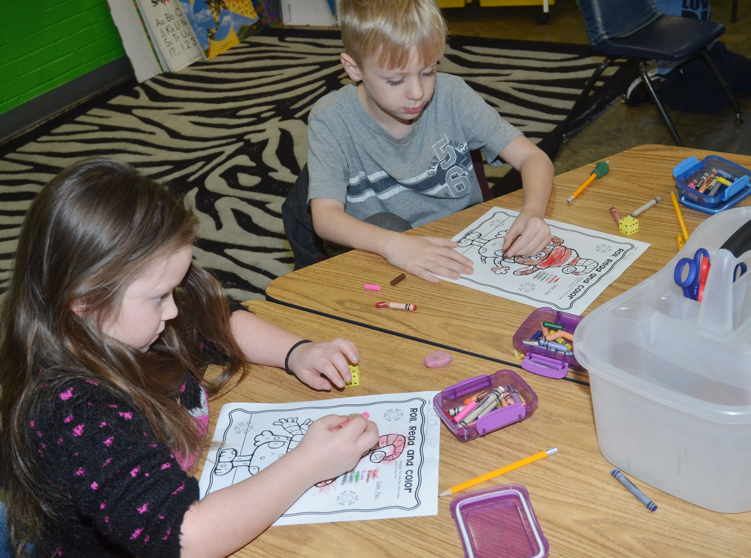 CES kindergarteners Gracie McKenzie, at left, and Lukas Adams roll the dice to see which numbers they are to color.