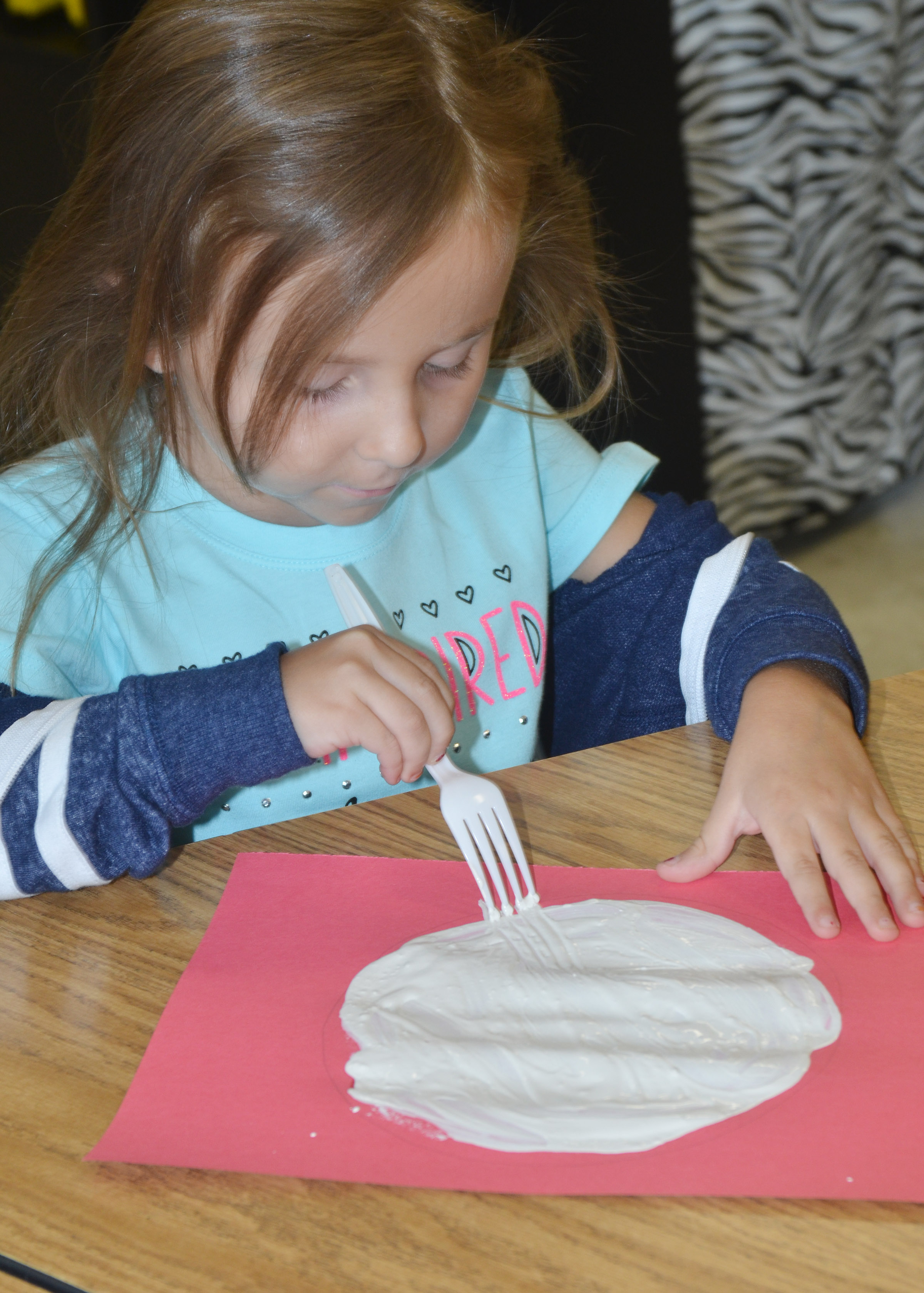 CES kindergartener Tabitha Leggett paints with a fork to make her panda's face.